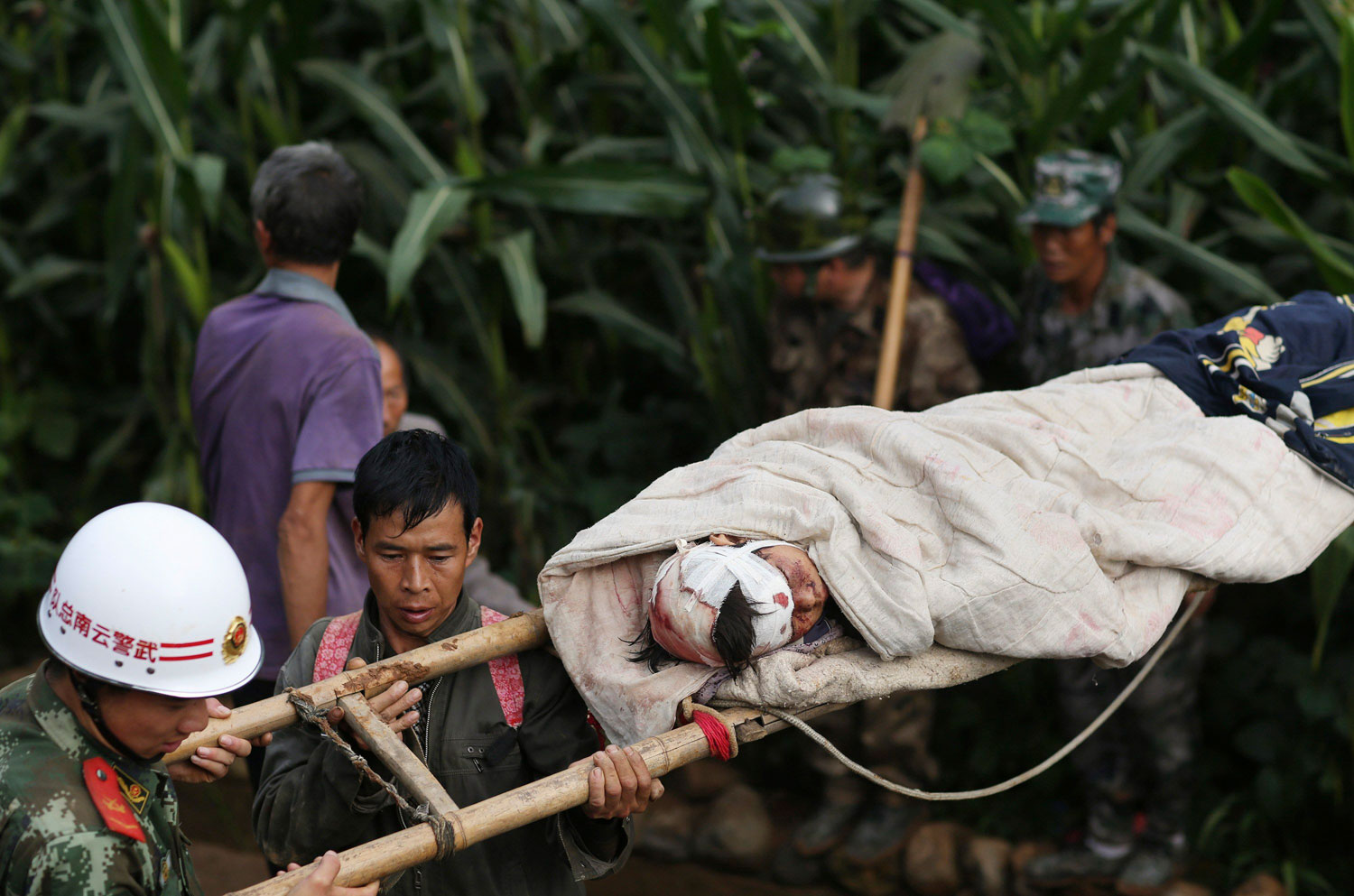 Rescuers carry an injured boy on a makeshift stretcher after an earthquake hit Longtoushan township of Ludian county, Yunnan province on Aug. 4, 2014.