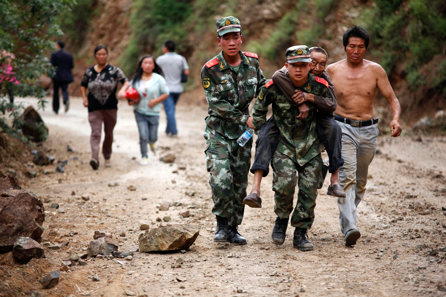 Paramilitary policemen evacuate an injured man after a deadly earthquake hit Longtoushan town, Ludian county, Zhaotong, Yunnan province on Aug. 3, 2014.