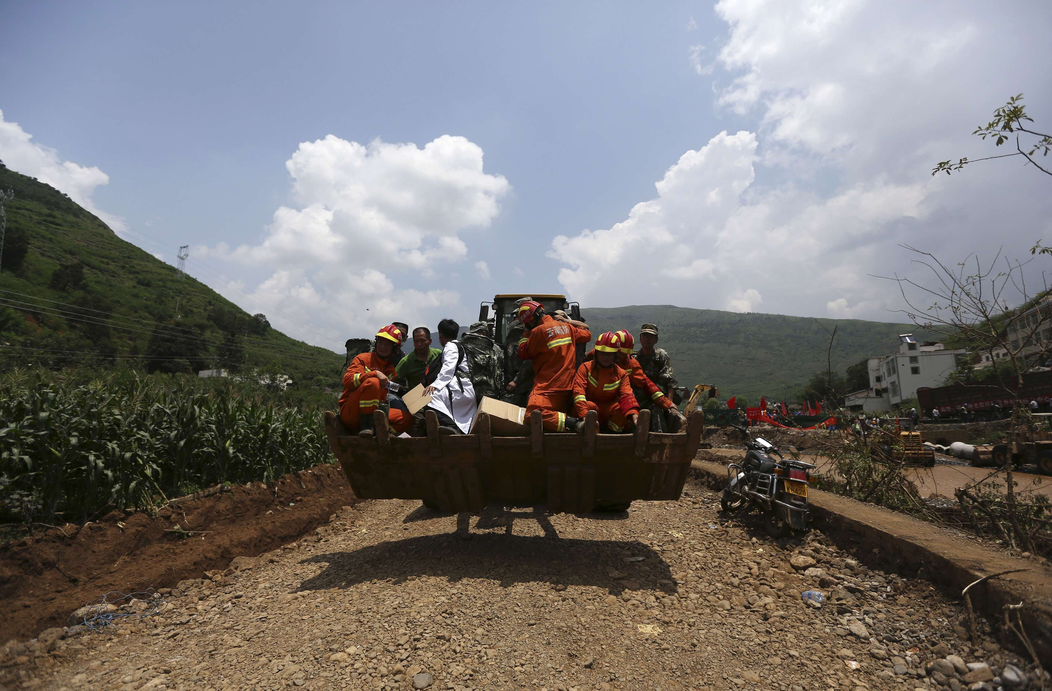 Rescue workers are transported into an earthquake zone on a front loader in Ludian county, Zhaotong, Yunnan province, August 5, 2014.