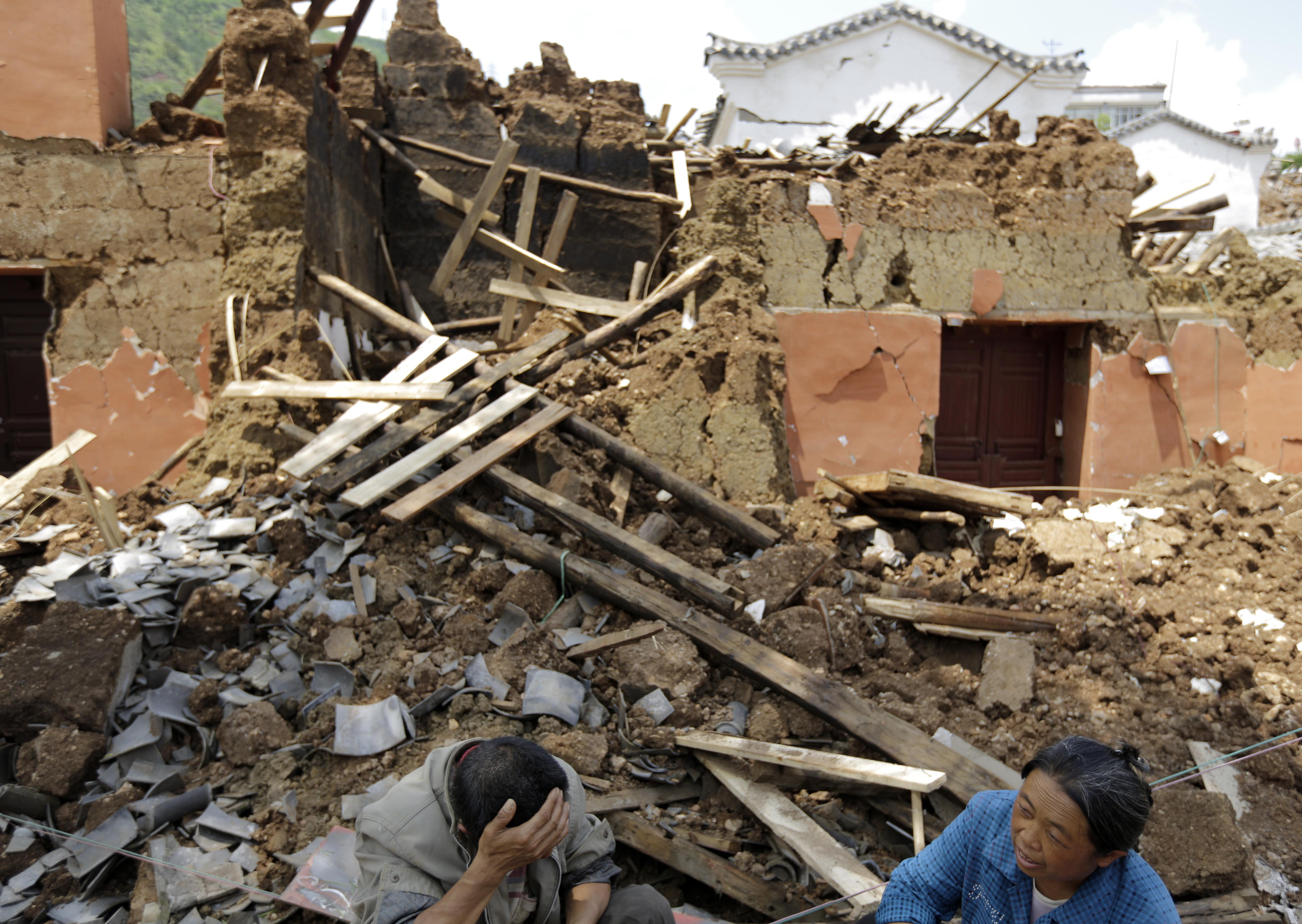 Villagers sit in front of their destroyed house following a massive earthquake in the town of Longtoushan in Ludian County in southwest China's Yunnan Province on Aug. 5, 2014.