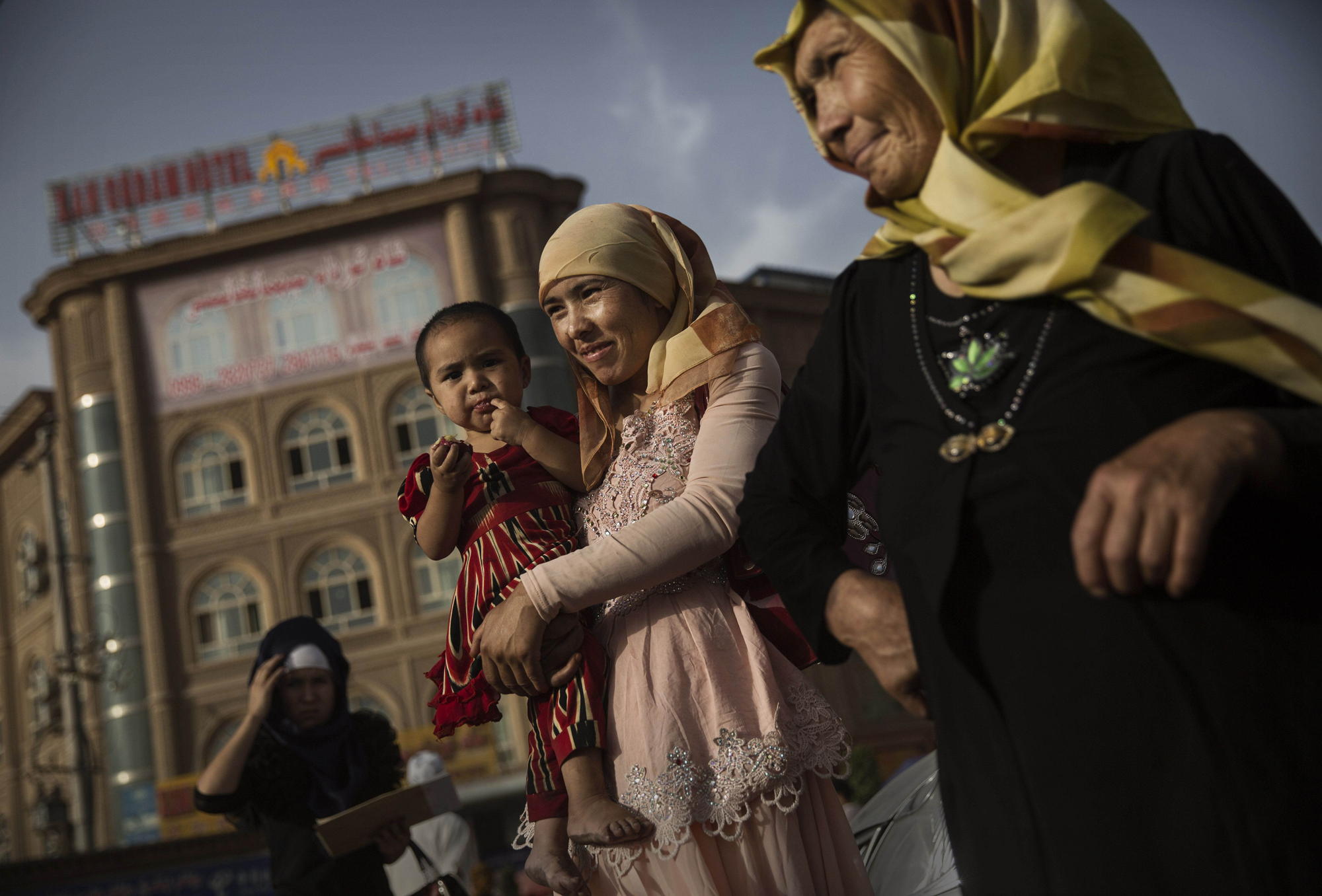 A Uighur woman walks with her baby at a market on August 1, 2014 in old Kashgar.