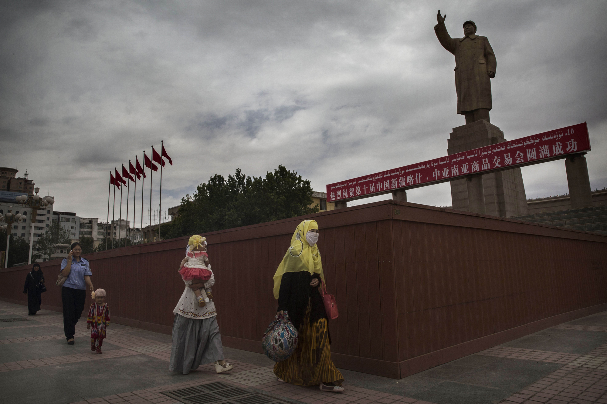 A veiled Muslim Uighur woman walks passed a statue of Mao Zedong on July 31, 2014 in Kashgar.