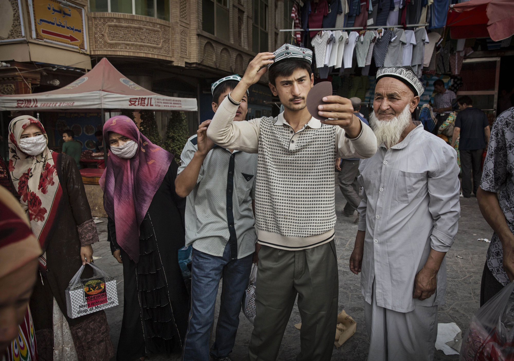 A Uighur man tries on a new traditional hat as he buys new clothes before the Eid holiday  on July 28, 2014 in old Kashgar.