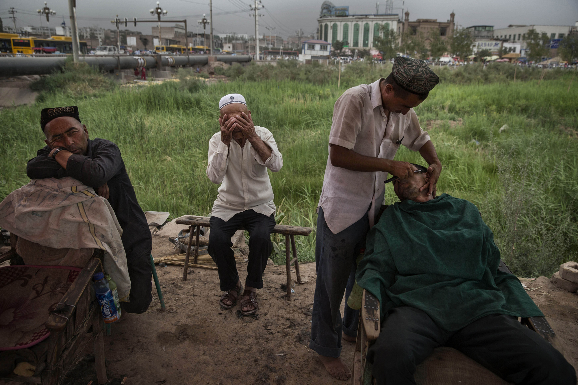 A Uighur shaves a customer at an outdoor stall before the Eid holiday  on July 28, 2014 in old Kashgar.
