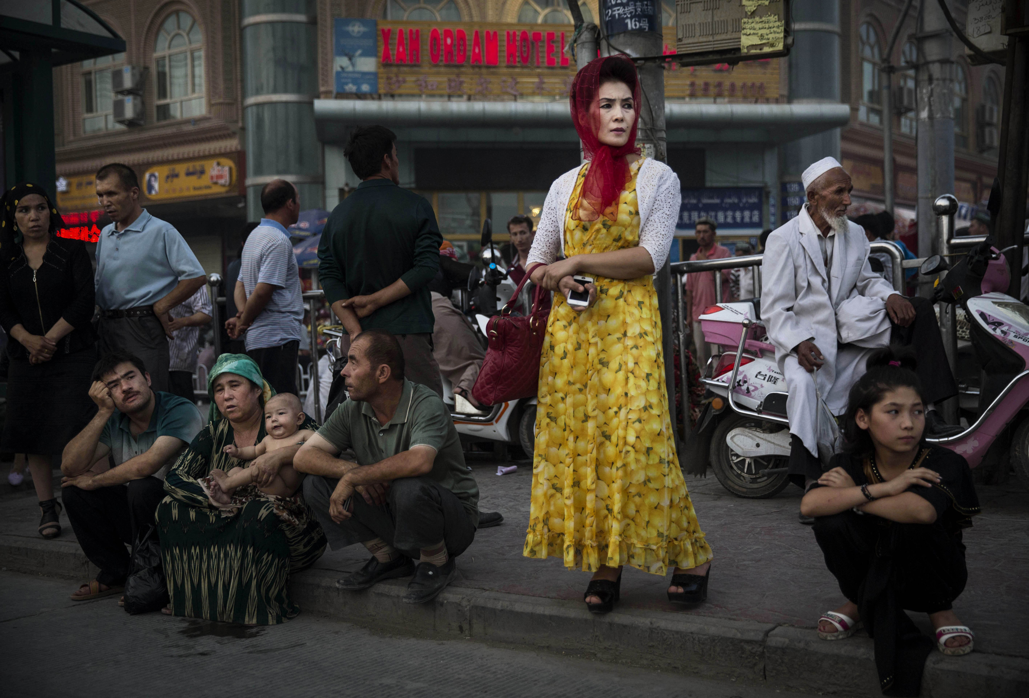 Uighurs wait at a bus stop on July 27, 2014 in old Kashgar.