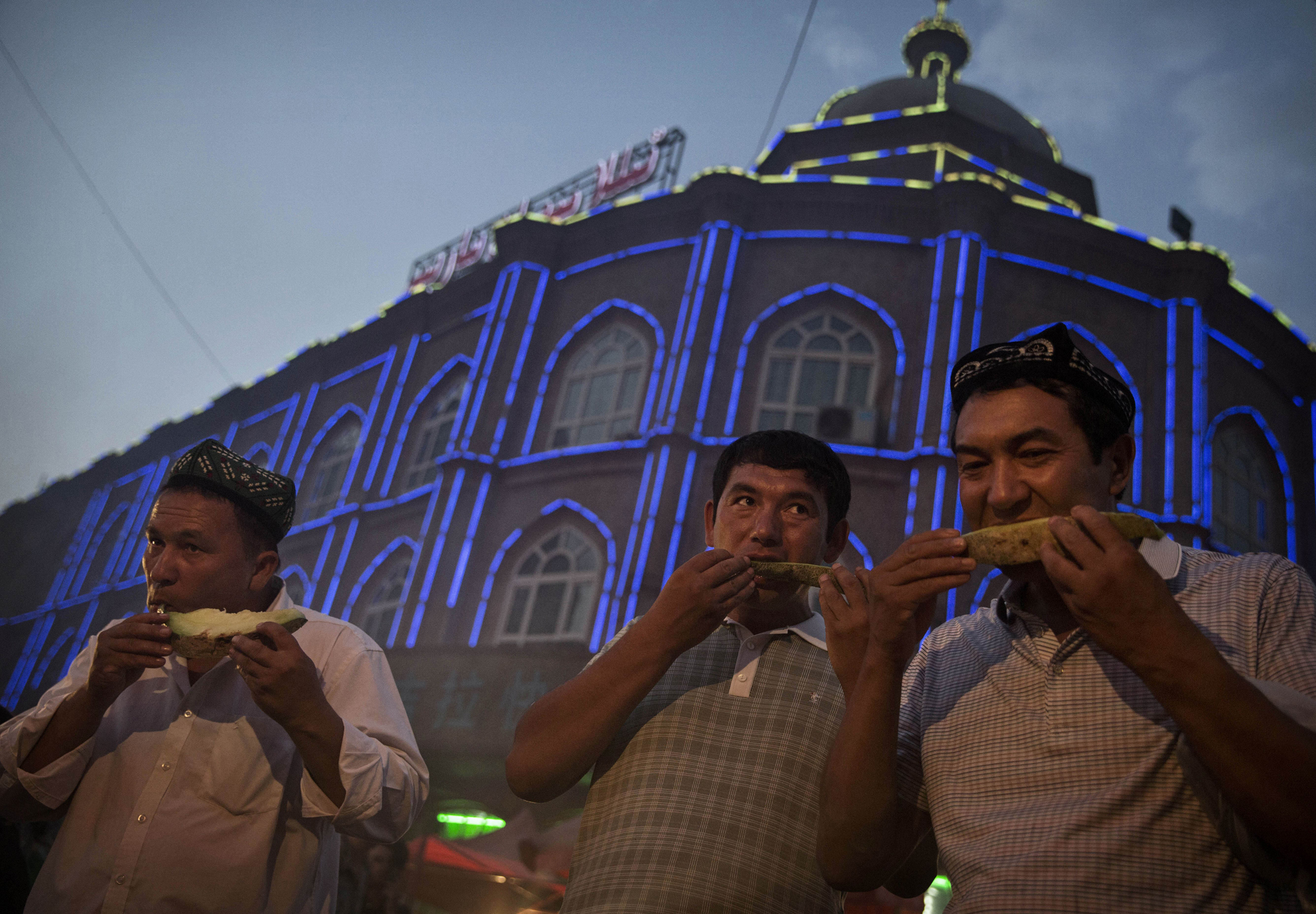 Uighur men eat melon as they break their Ramadan fast before the Eid holiday at a night market on July 28, 2014 in old Kashgar.