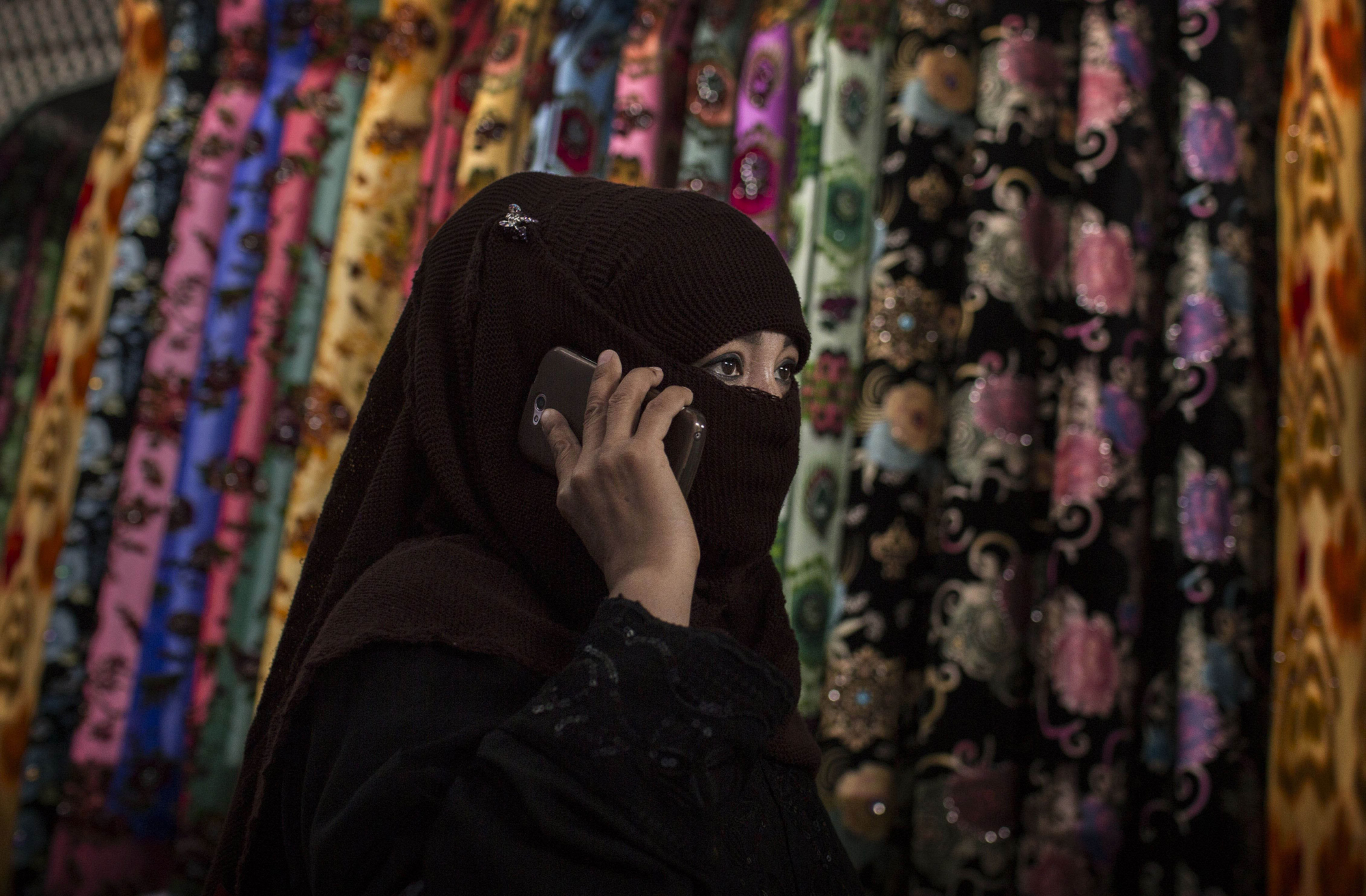 A Uighur woman wears a veil as she shops at a local market on August 2, 2014 in Kashgar.