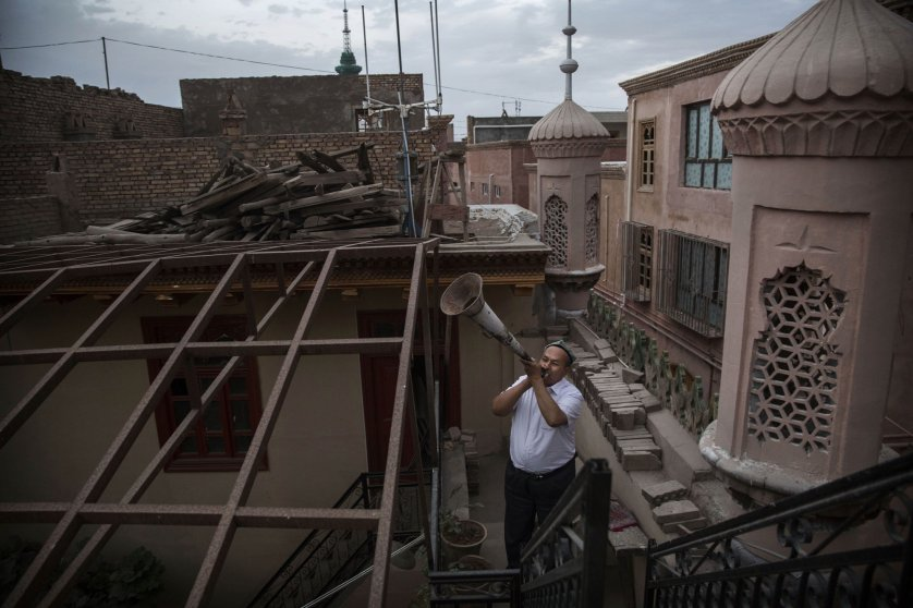 A Uyghur Muslim muezzin uses a bullhorn to call the evening prayers on July 30, 2014 in Kashgar.