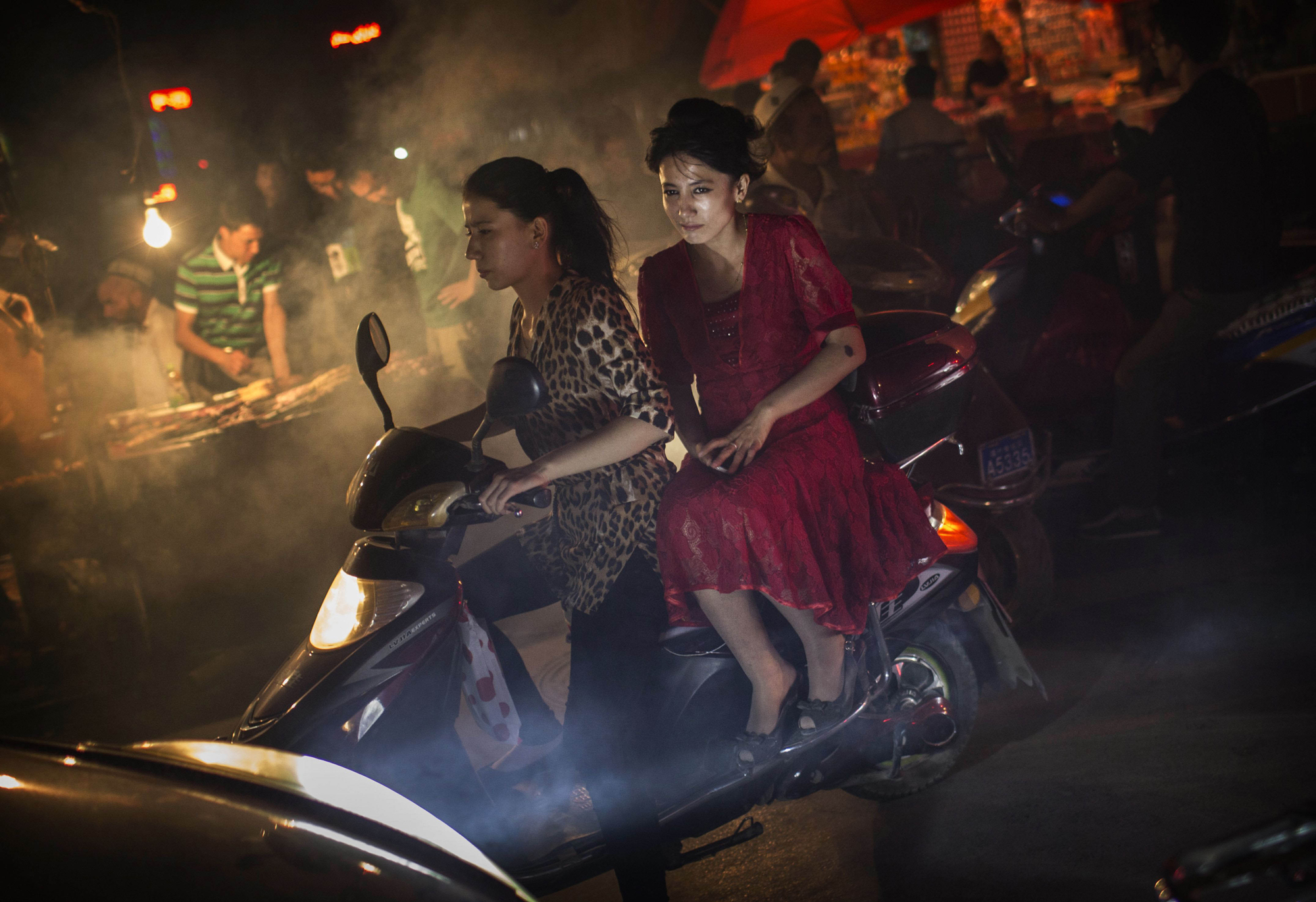 Uighur women without veils ride on a scooter in a market on July 27, 2014 in old Kashgar.