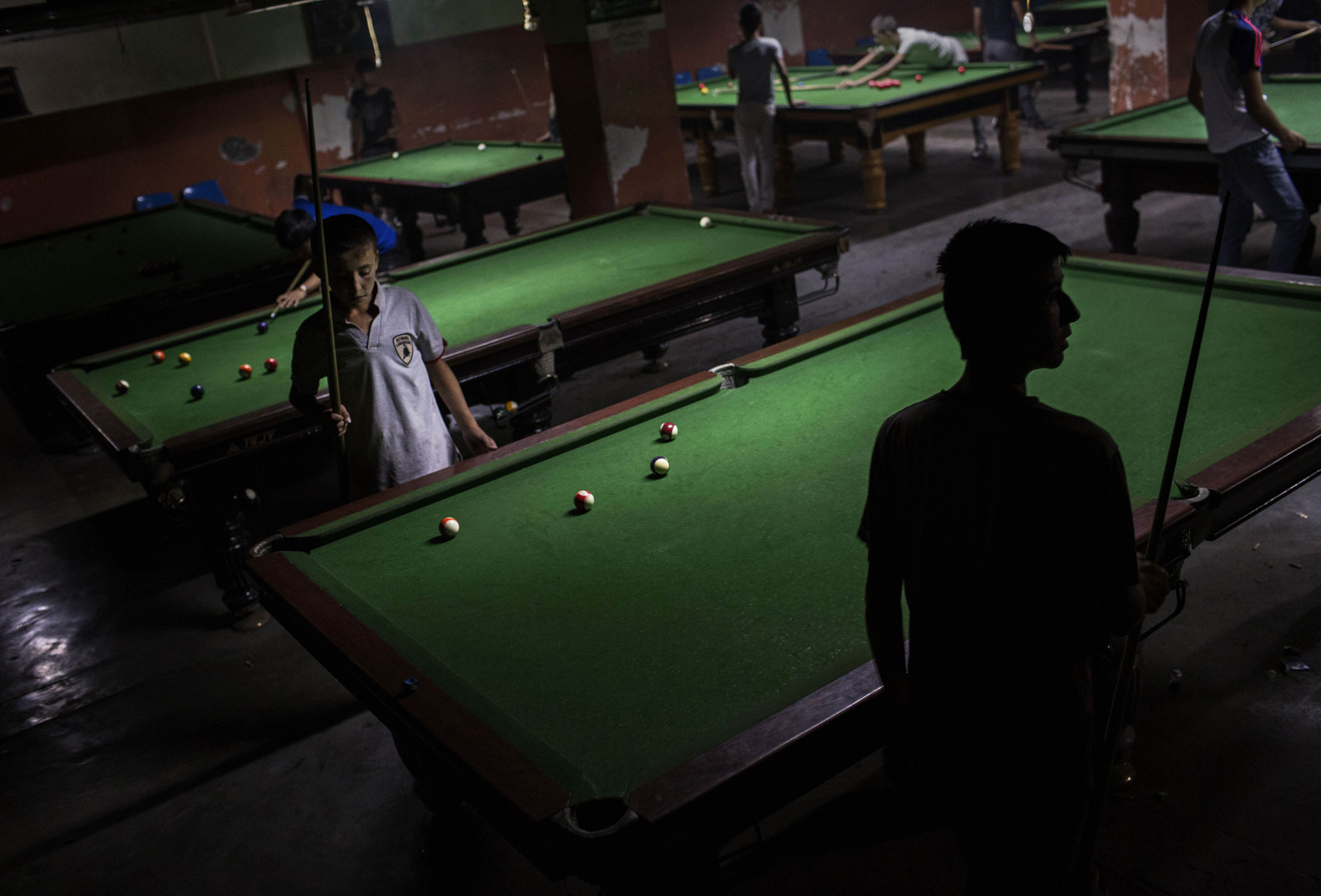 Uighur youth play pool at a billiard hall on August 2, 2014 in Kashgar.