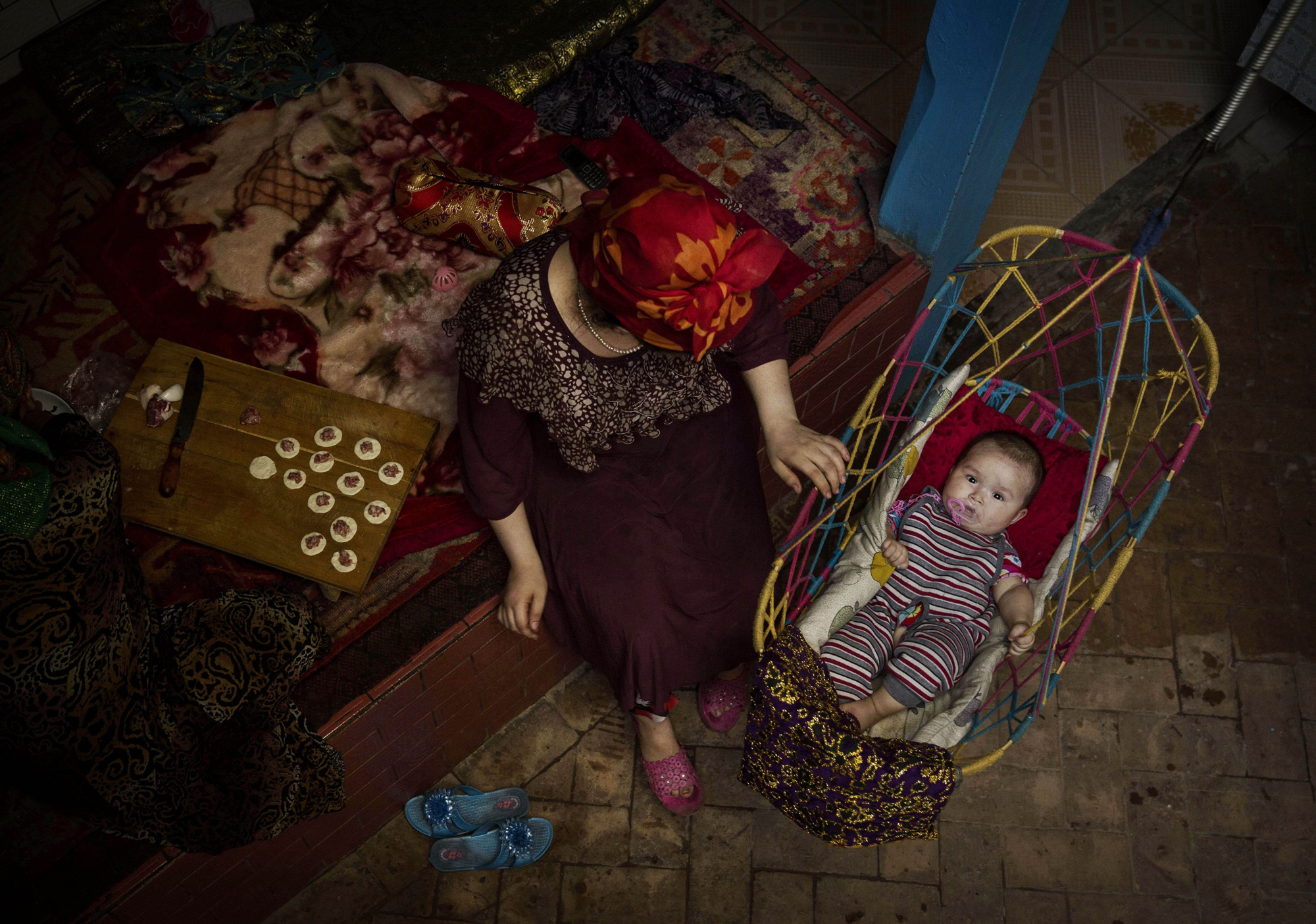 A Uighur woman takes care of her child at home before the Eid holiday  on July 28, 2014 in old Kashgar.