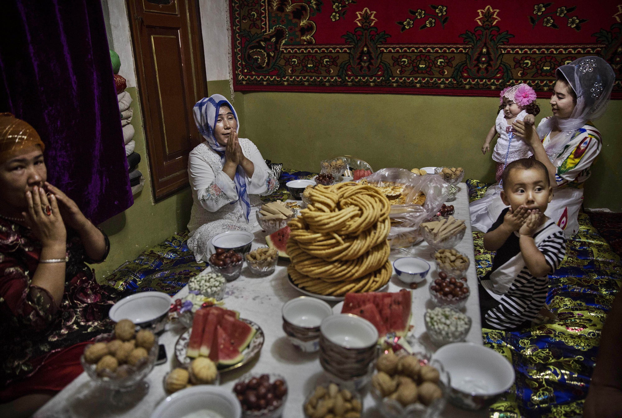 A Uighur family pray before lunch on the Eid holiday on July 29, 2014 in old Kashgar.