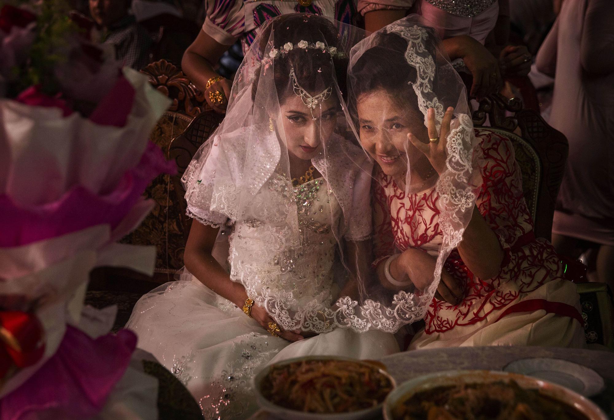 A Uighur bride talks with a friend at her  wedding celebration on August 2, 2014 in Kashgar.