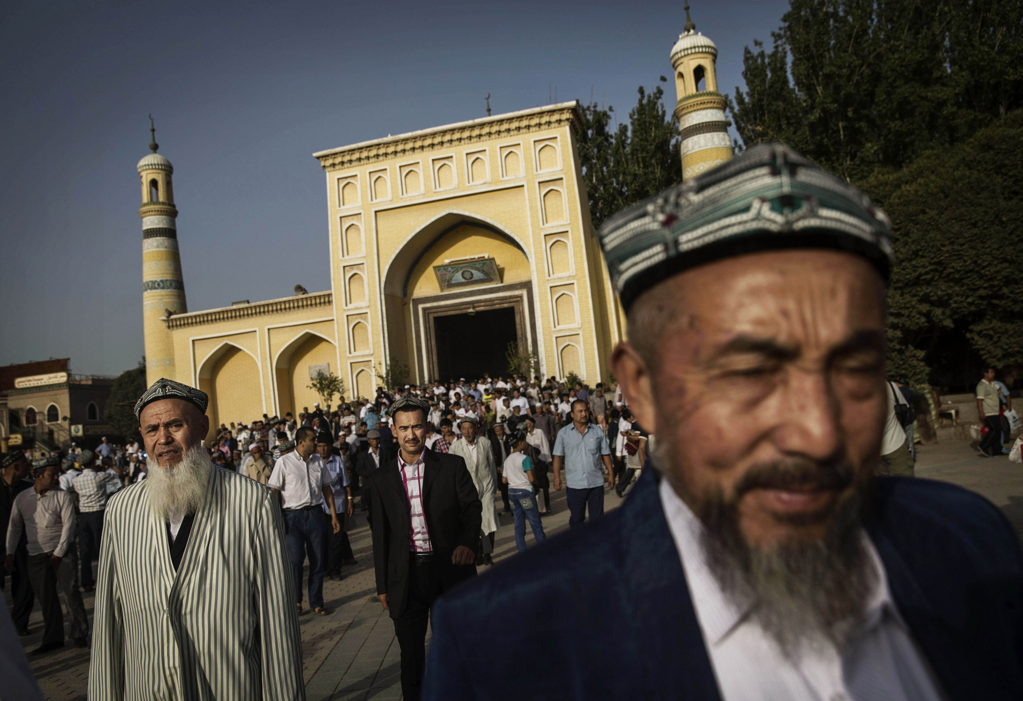 Uighur men leave the Id Kah Mosque following the Eid prayers on July 29, 2014 in old Kashgar, Xinjiang Province, China.