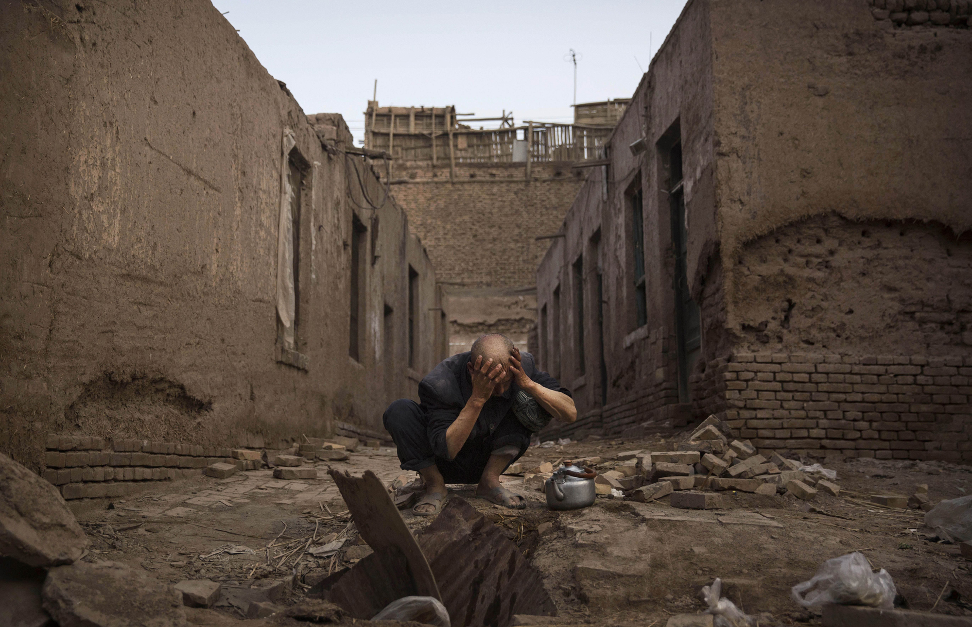 A Uighur man washes himself before prayers next to abandoned traditional houses set to be demolished by authorities to make way for new homes on July 27, 2014 in old Kashgar.