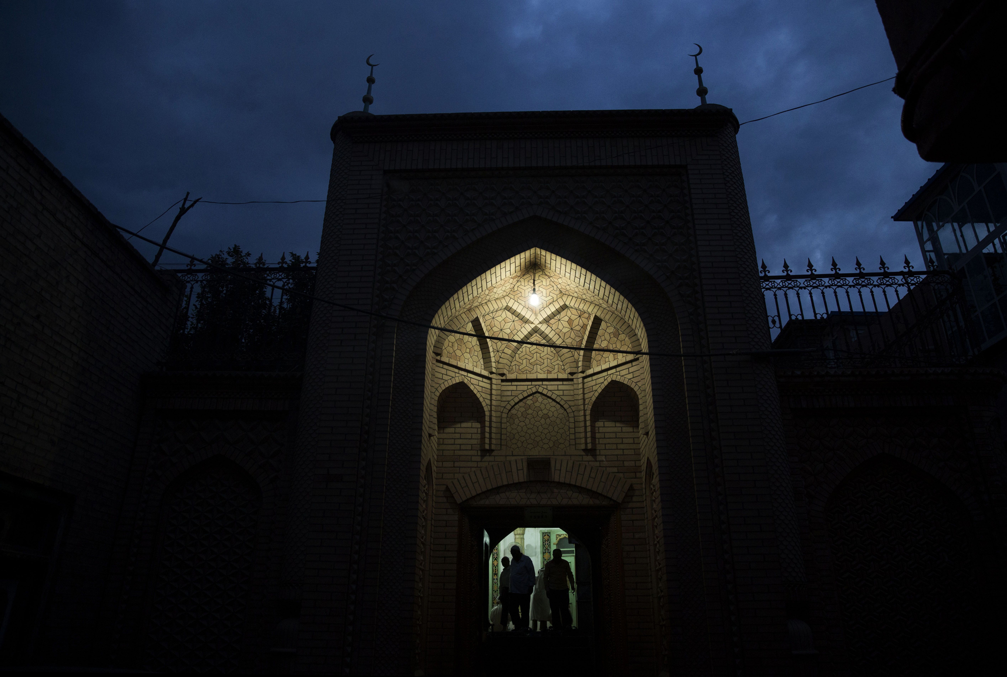 Uighur men leave a mosque after evening prayers on July 30, 2014 in Kashgar.