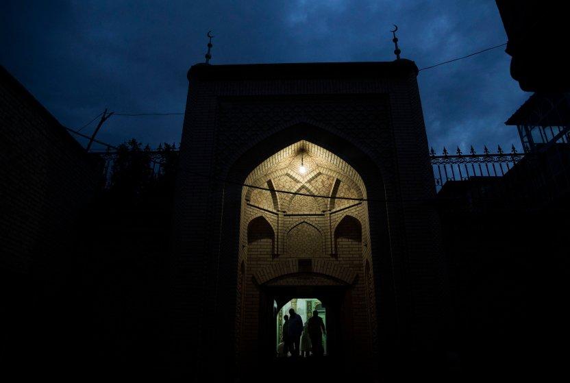 Uyghur men leave a mosque after evening prayers on July 30, 2014 in Kashgar.