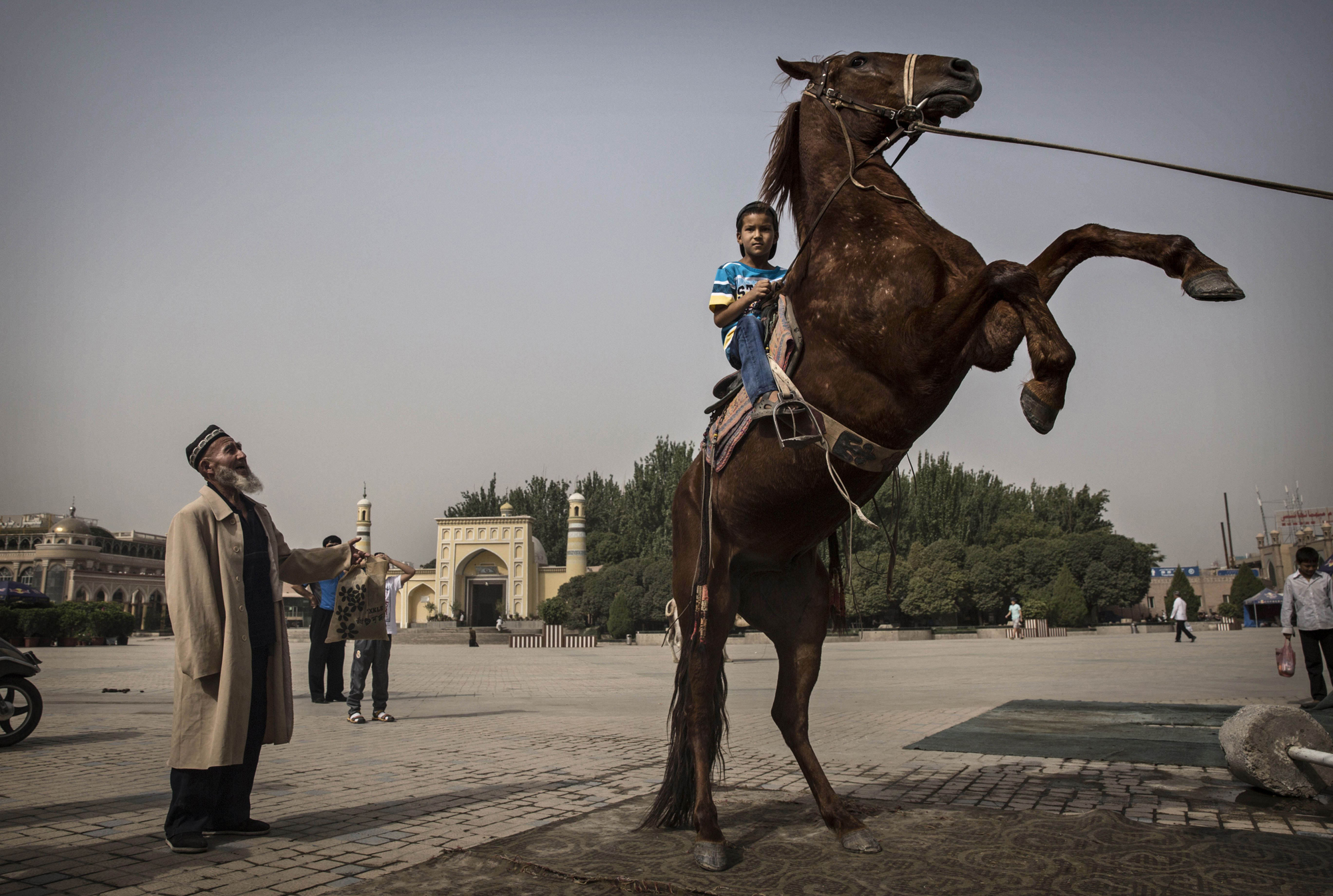 A Uighur boy sits atop a horse as he has his picture taken outside the Id Kah Mosque before the Eid holiday  on July 28, 2014 in old Kashgar.