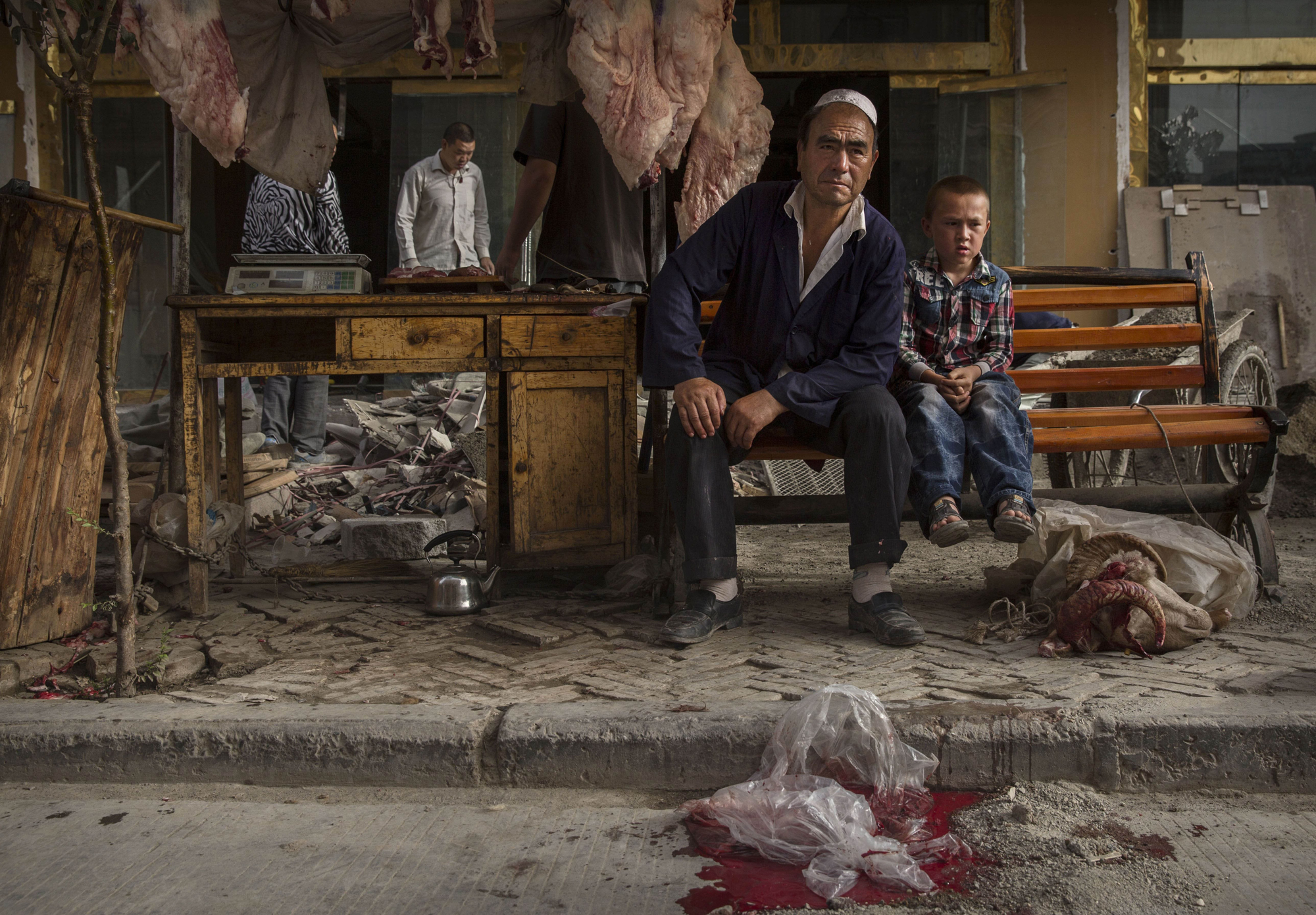 A Uighur butcher and his son wait for customers before the Eid holiday on July 28, 2014 in old Kashgar.