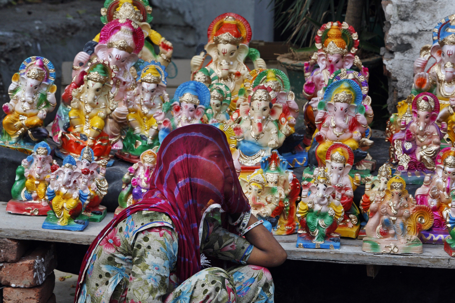 Aug. 29, 2014. An Indian vendor awaits customers as she sells idols of elephant-headed Hindu god Ganesh on the first day of the Ganesh Chaturthi festival in Jammu, India.