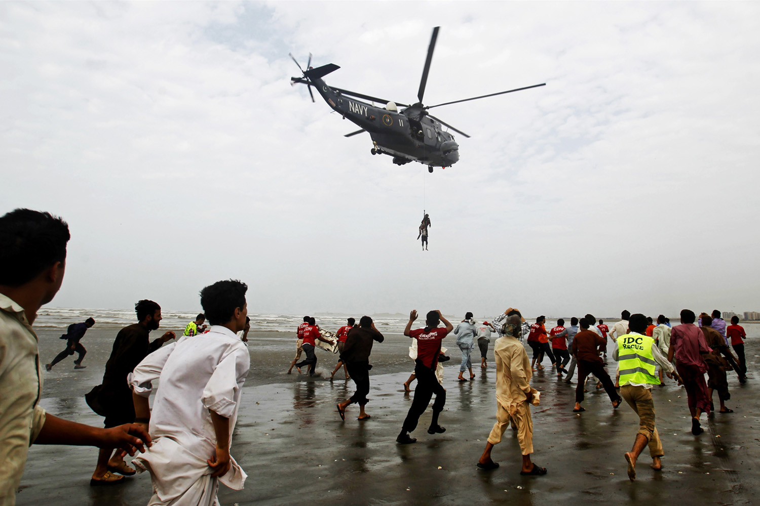 Jul. 31, 2014. A Pakistan Navy helicopter evacuates a recovered body of a victim who drowned over Clifton beach in Karachi, Pakistan. Scores of people drowned despite a ban on entering and bathing in the sea due to high tides, after thousands of people turned up on various beaches of Karachi to celebrate Muslims festive day of Eid.