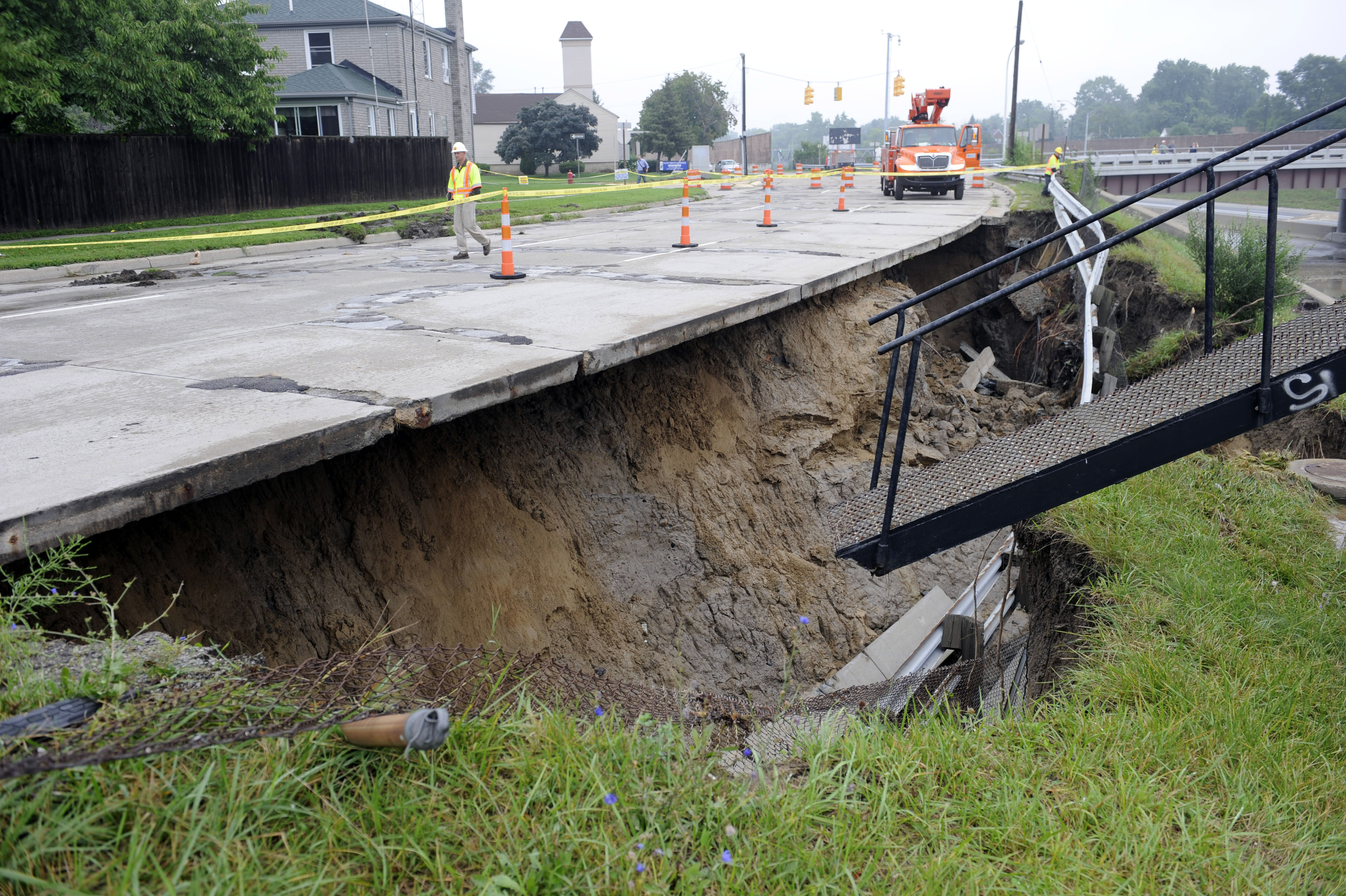 The west service drive of I-75 is washed out under the roadway in Madison Heights, Mich. on Aug. 12, 2014. Fearing more motorists could become stranded a day after a storm dumped more than 6 inches of rain in some places in and around Detroit, the state warned commuters against driving in affected areas Tuesday morning.