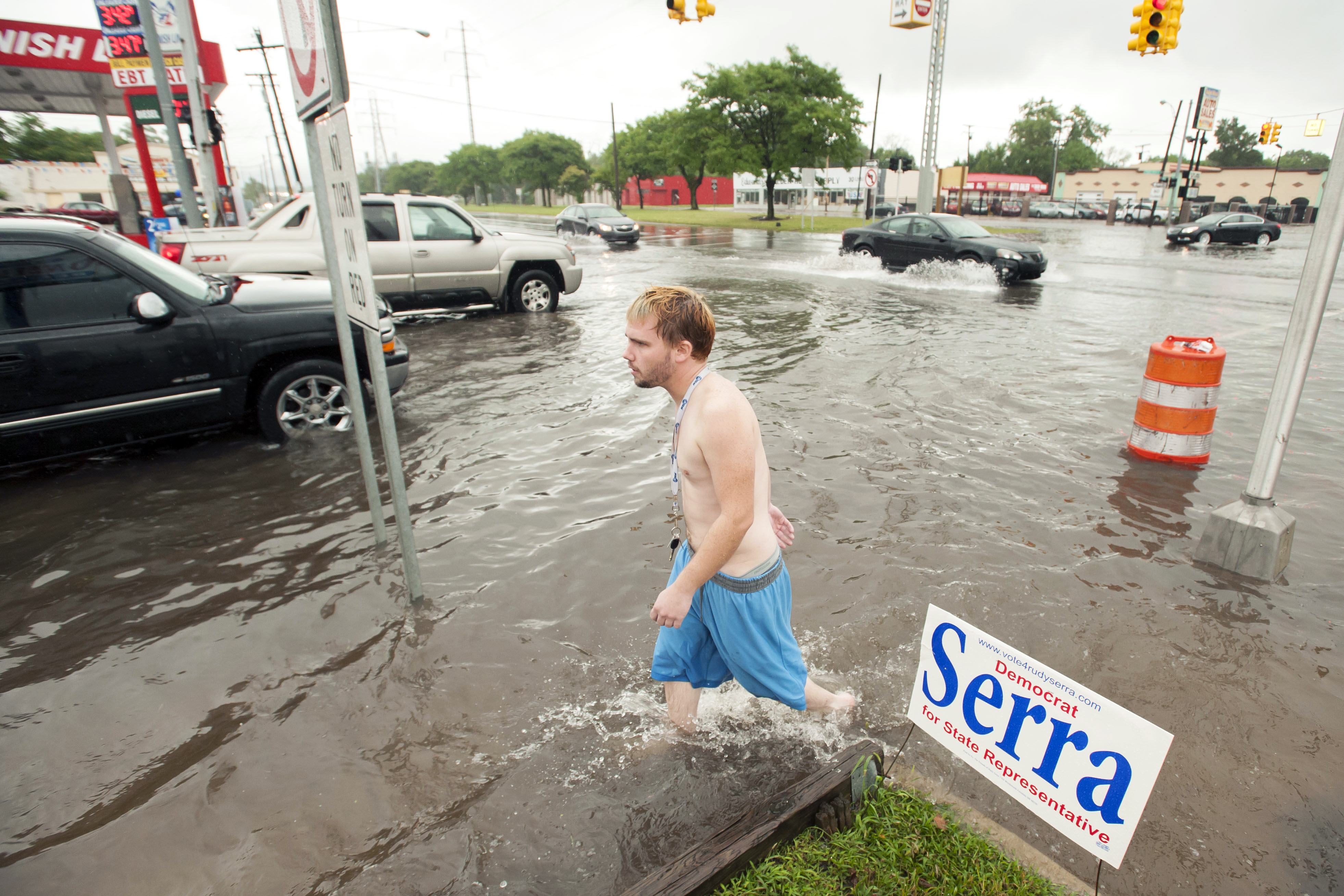 Joe Snyder, of Warren, Mich., walks through the flooded streets of Detroit on Aug. 11, 2014. Fearing more motorists could become stranded a day after a storm dumped more than 6 inches of rain in some places in and around Detroit, the state warned commuters against driving in affected areas Tuesday morning.