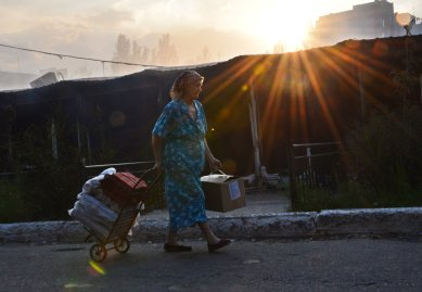 A woman walks by a burning local market after shelling in the town of Yasynuvata, near the rebel stronghold of Donetsk, eastern Ukraine on August 12, 2014.