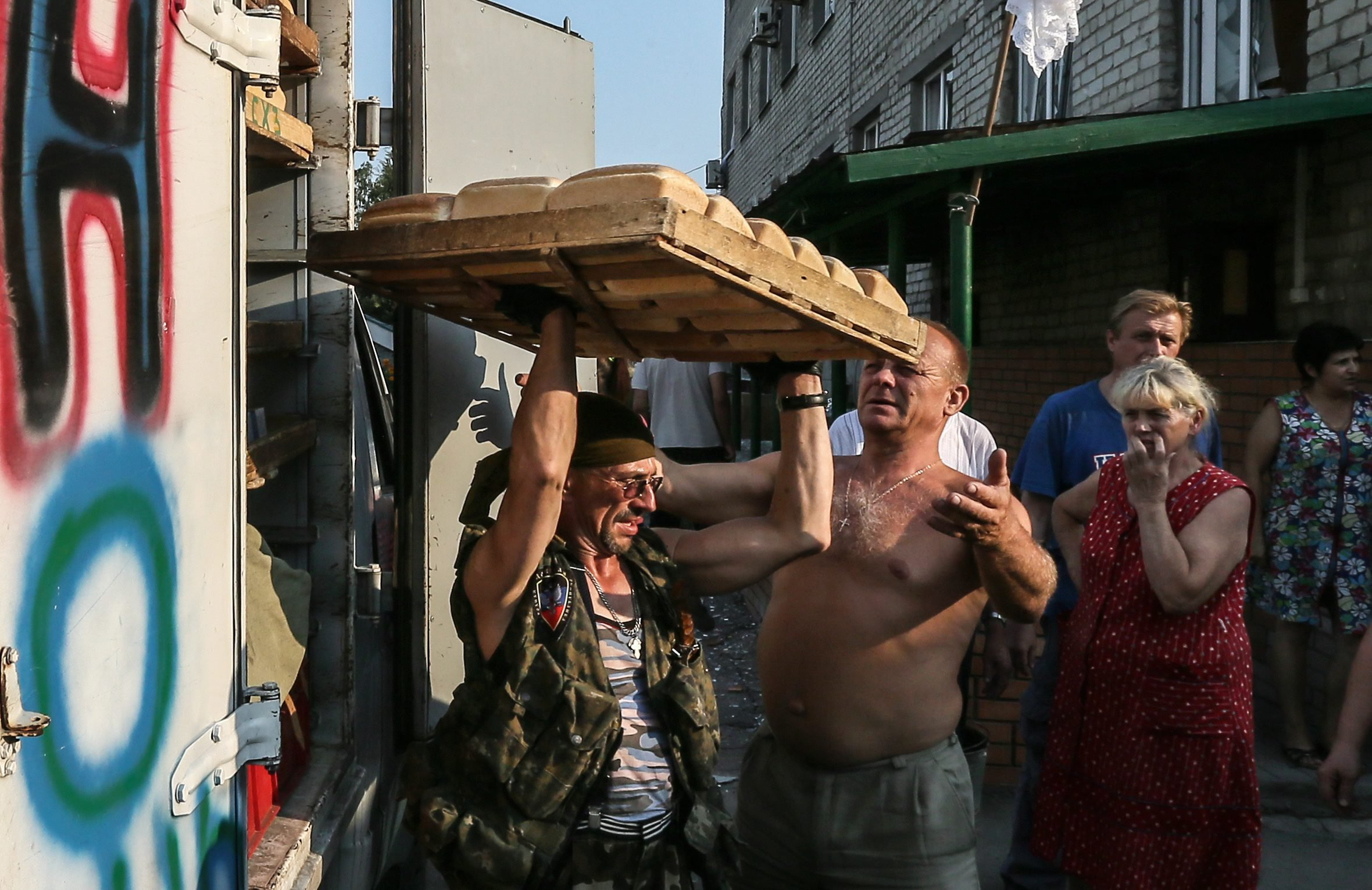 Member of the Donetsk People's Republic militias carry trays with bread for locals hiding in shelters in Ilovaysk 50km from Donetsk, Ukraine on August 14, 2014.