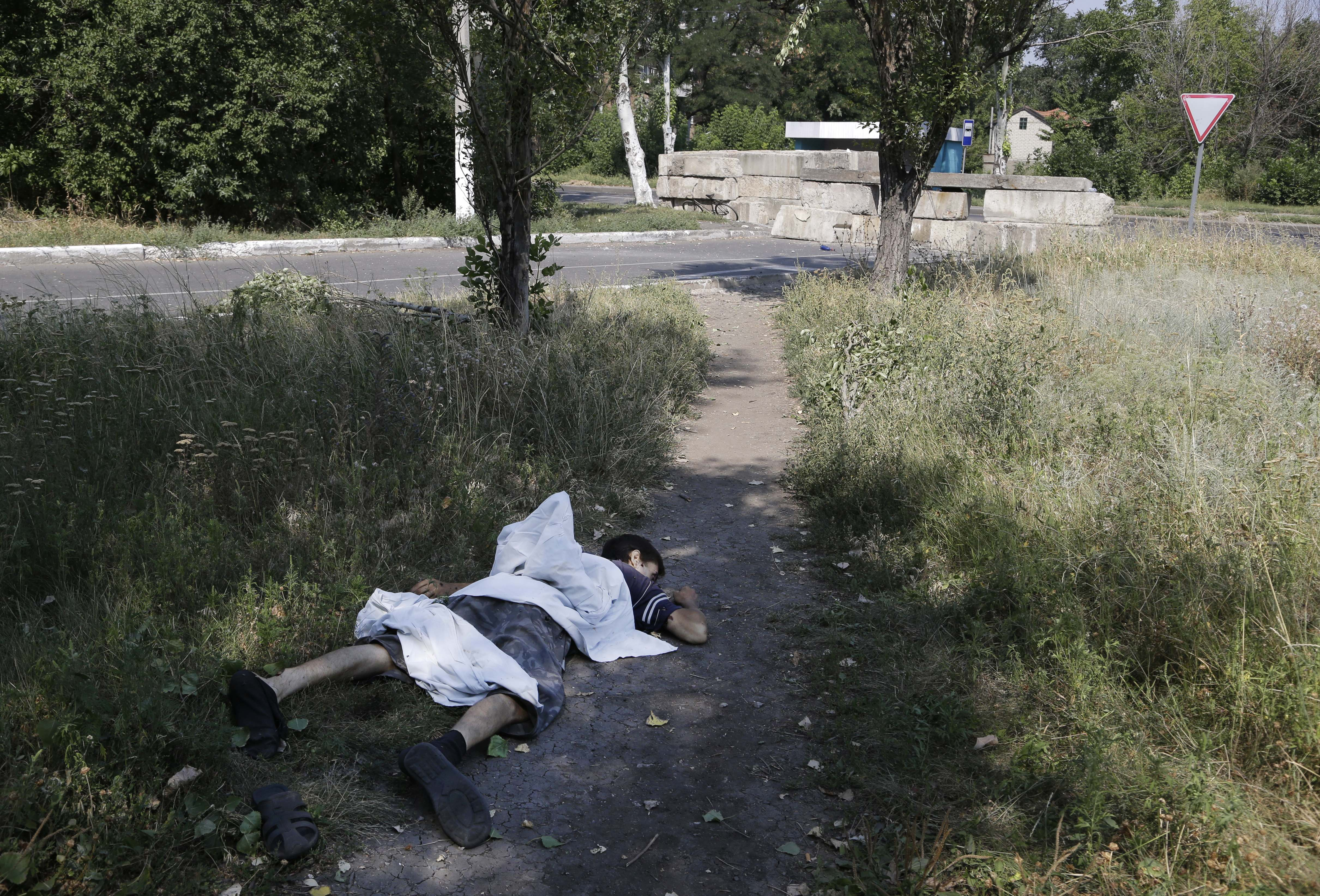 A dead body lies in a street in the city's southwestern Petrovsky district after shelling in Donetsk, eastern Ukraine on August 13, 2014.
