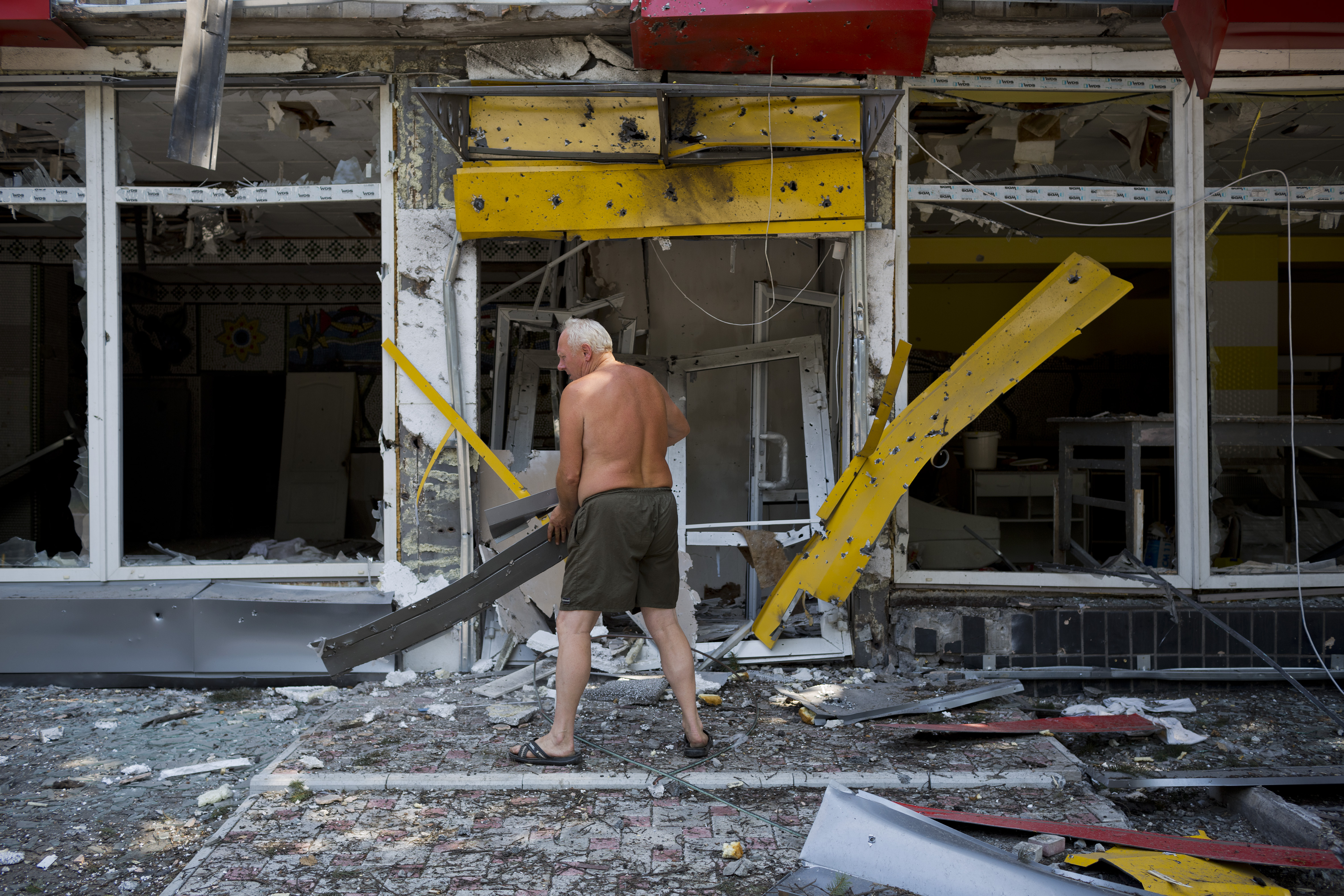A man clears debris as the Ukrainian army retakes a village from pro-Russian rebels onAugust 13, 2014 in Uglegorsk. Ukraine.