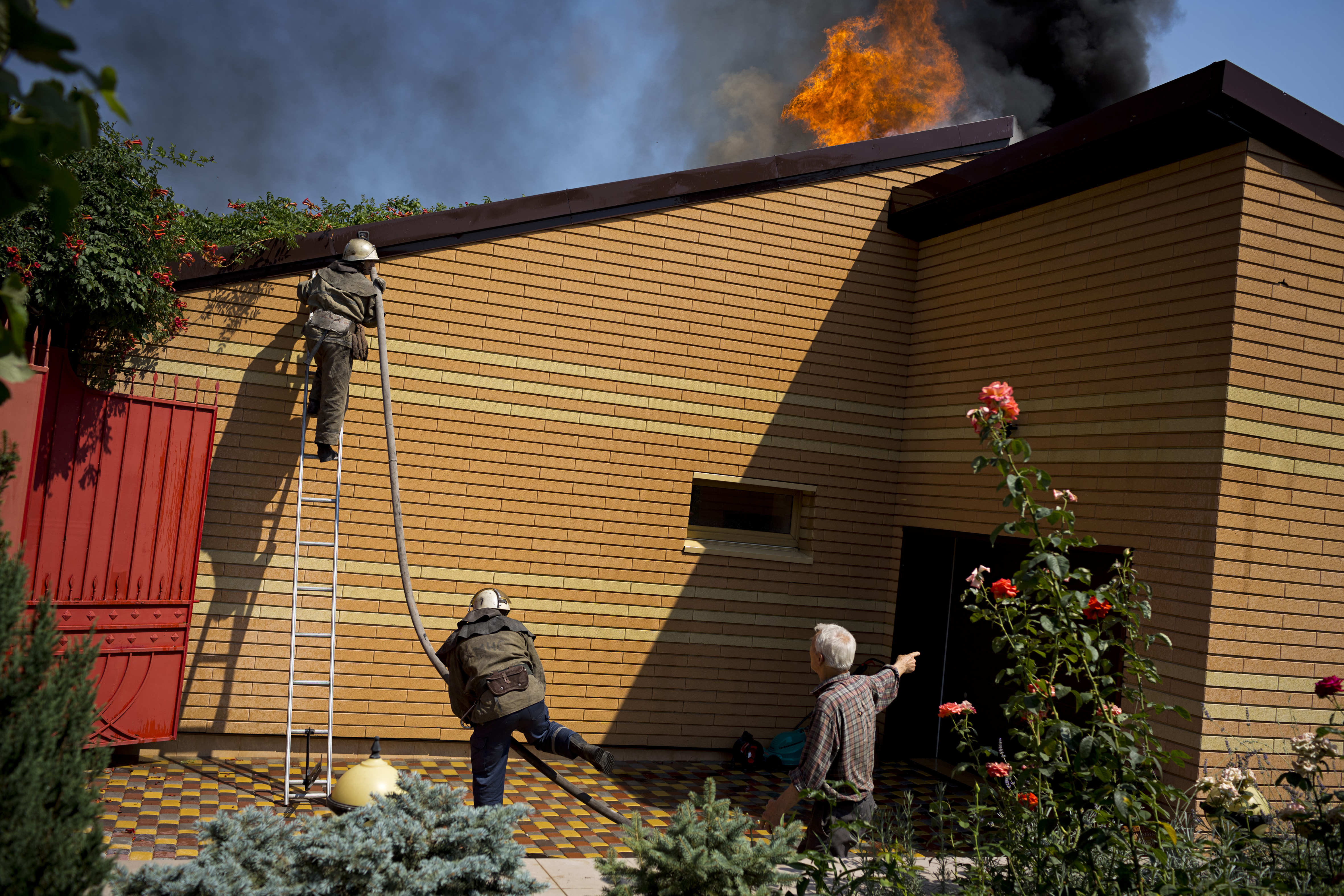 Firemen try to put out a fire in Voroshyloskyi, a residential area of Donetsk, after it was hit by artillery shelling on August 14, 2014 in Ukraine.