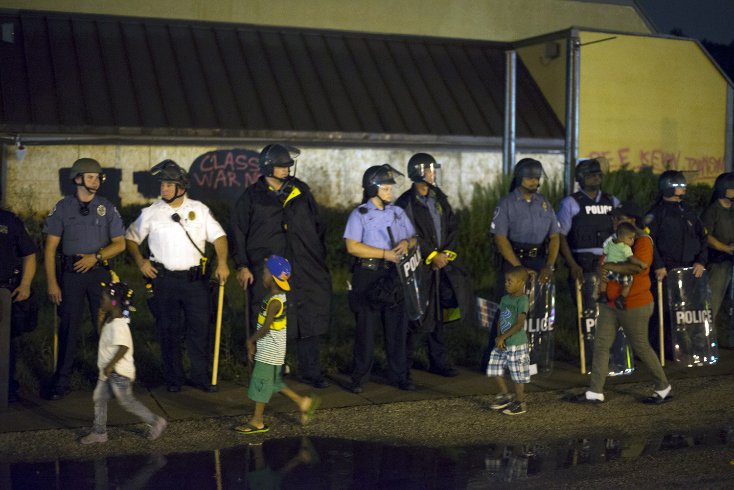 Children walk past police officers during a demonstration in Ferguson, Mo. on Aug. 16, 2014.