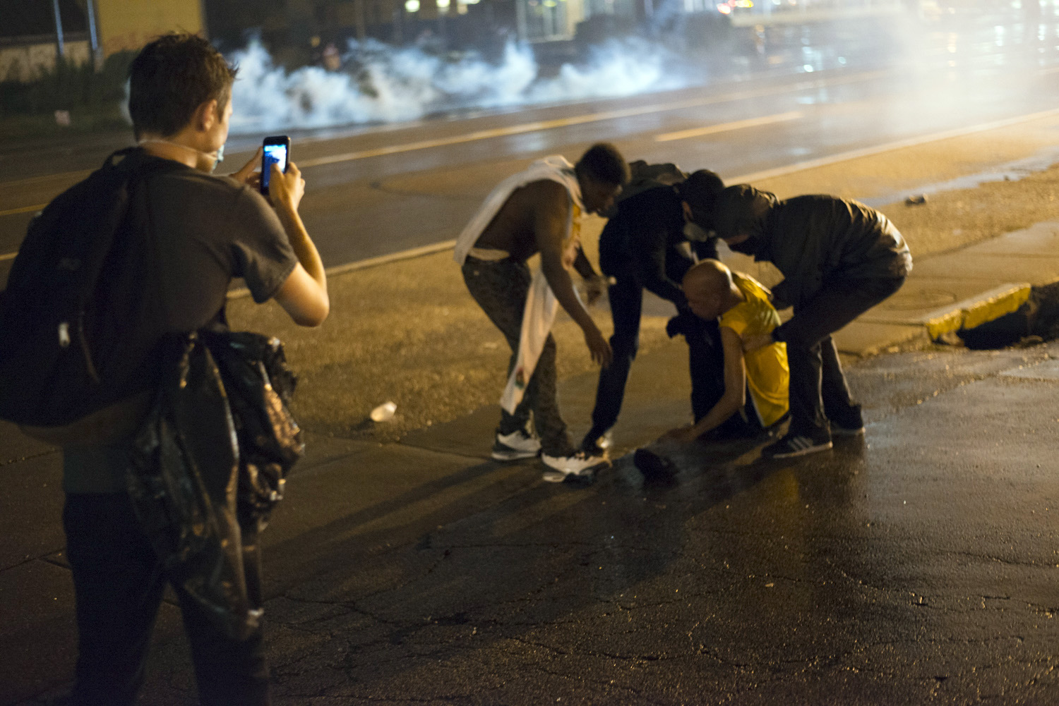 Protestors help a man who was injured by tear gas thrown by police after refusing to disperse after the midnight curfew in Ferguson, Mo. on Aug. 17, 2014.