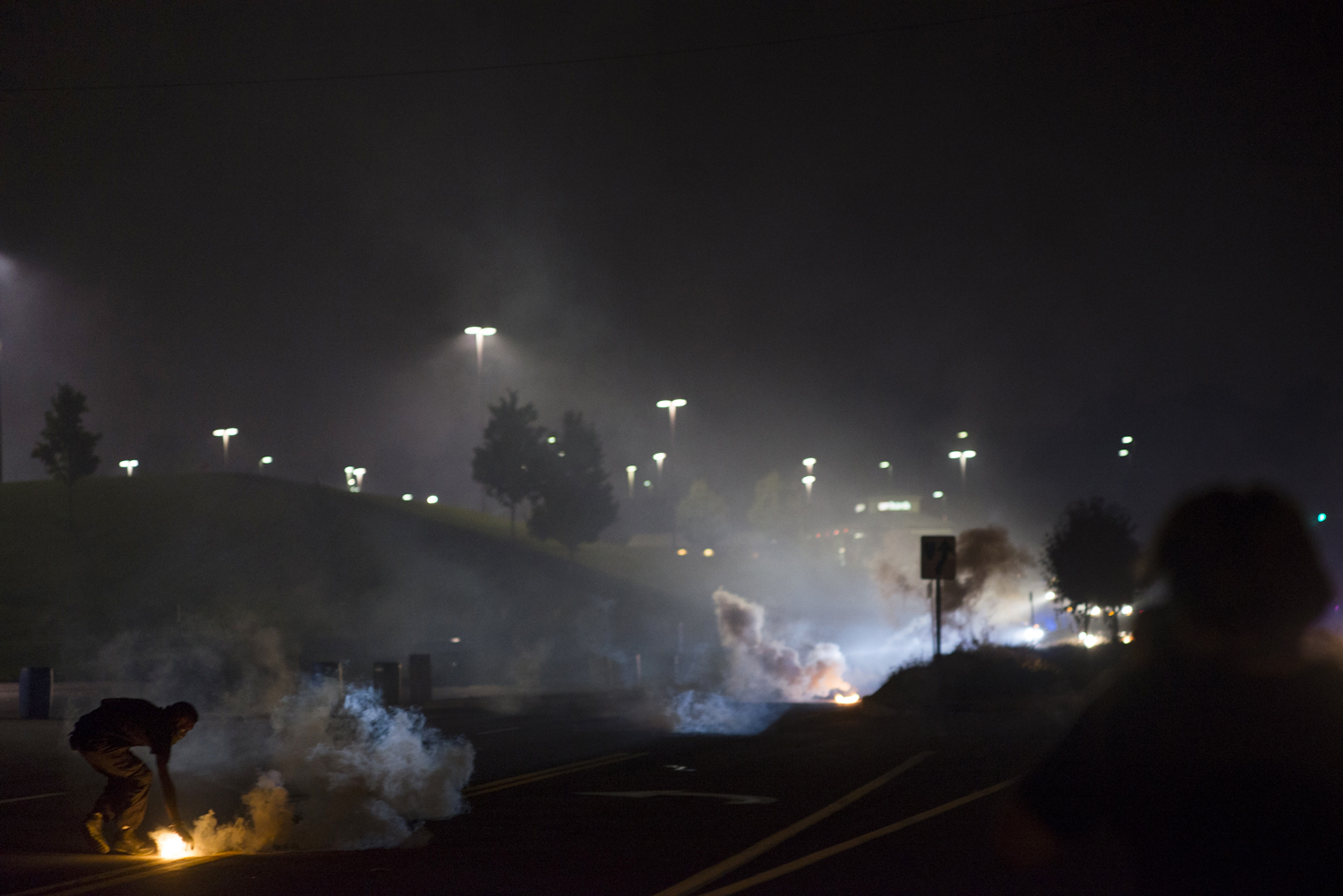 A protestor throws a canister of tear gas back at police during demonstrations in Ferguson, Mo. on Aug. 17, 2014.