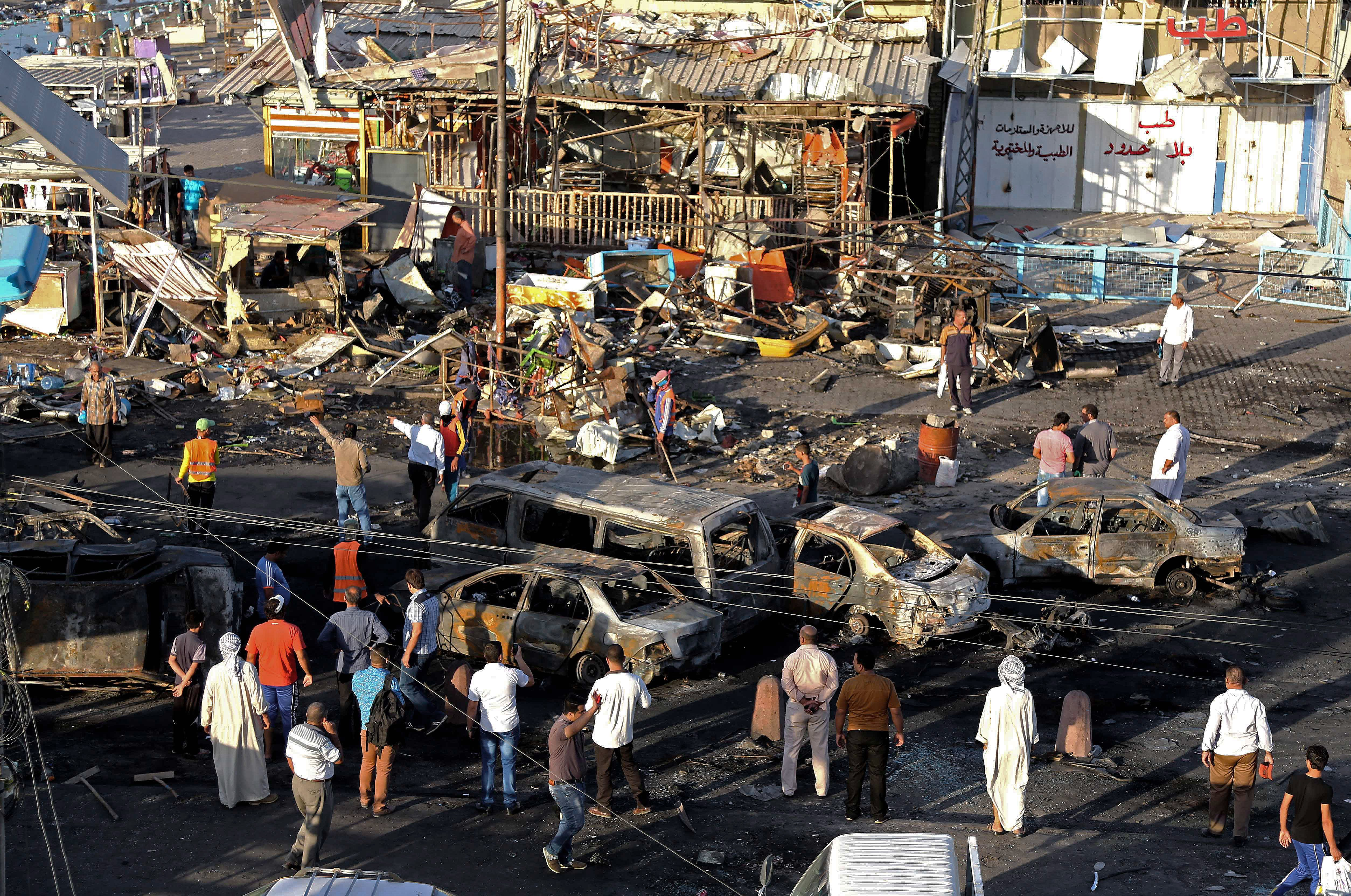 Aug. 7, 2014. Iraqi civilians gather the morning after a string of car bombs tore through busy shopping streets in several neighborhoods in Baghdad, Iraq. At least 50 people were killed as the army announced that one of its airstrikes had killed tens of militants in the northern city of Mosul.
