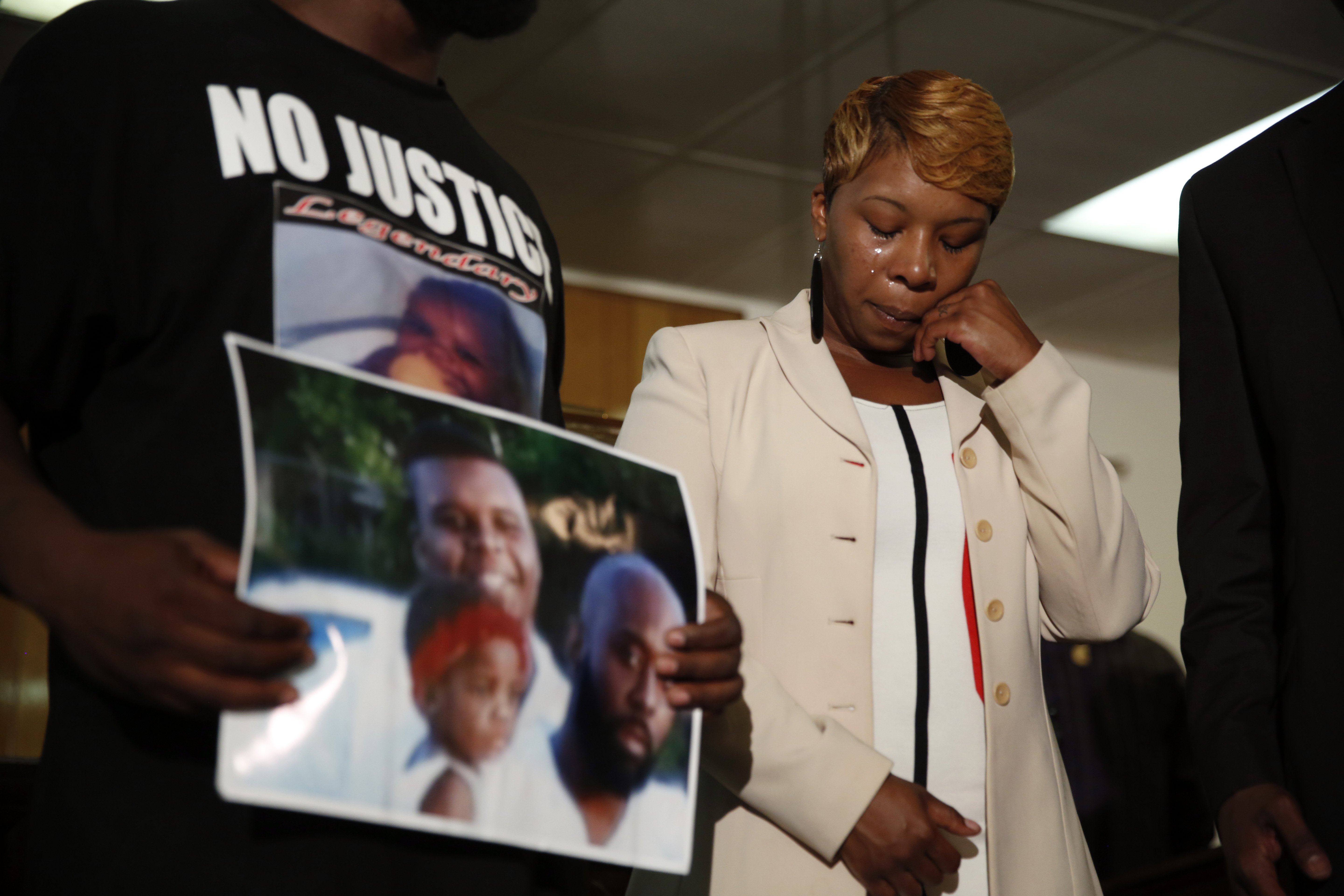 Lesley McSpadden, the mother of 18-year-old Michael Brown, wipes away tears as Brown's father, Michael Brown Sr., holds up a family picture of himself and his son during a news conference on August 11, 2014, in Ferguson, Mo.