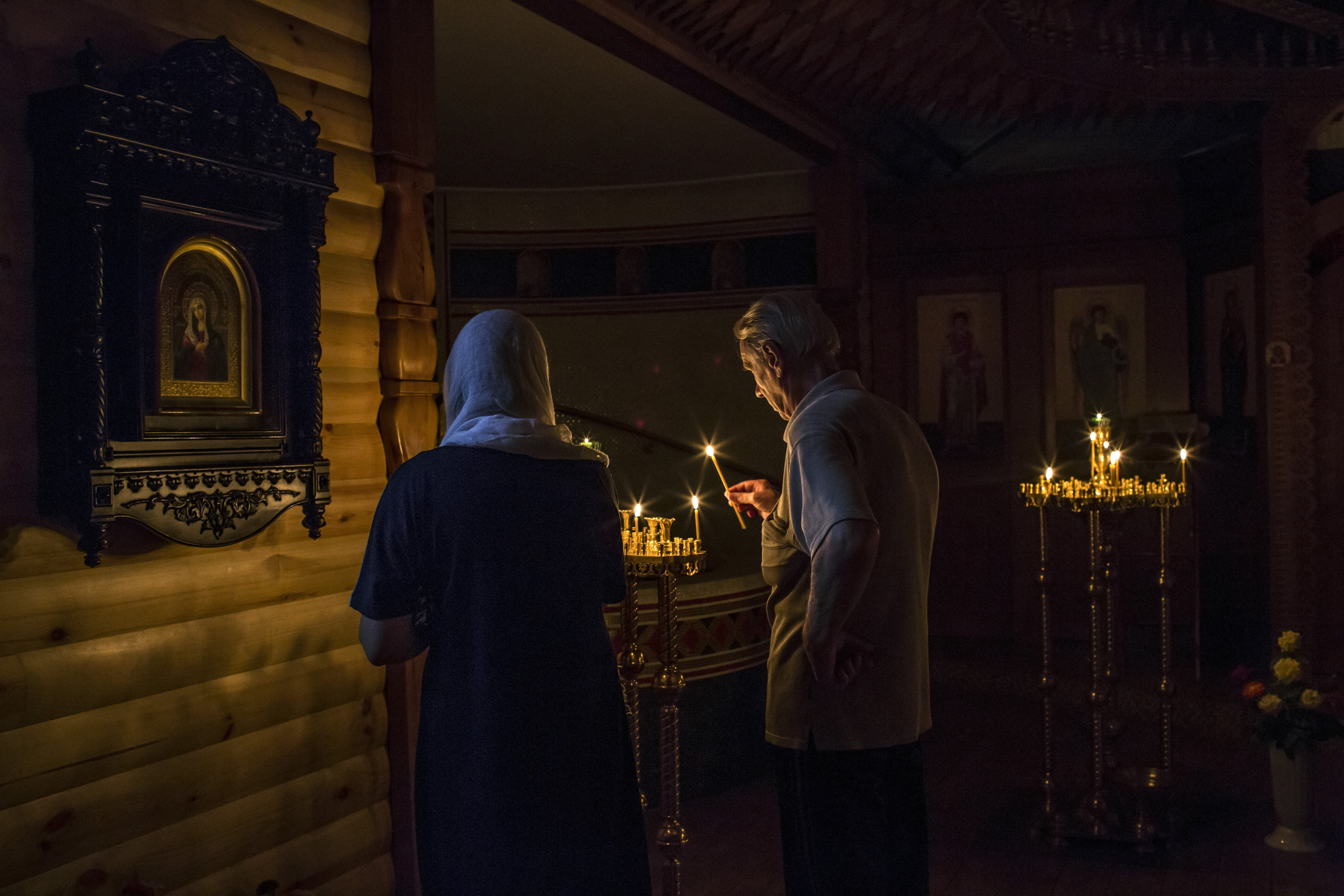 A couple lights a candle as they pray in a lower room of a church which was reportedly damaged by shelling in Luhansk, Ukraine on August 14, 2014.