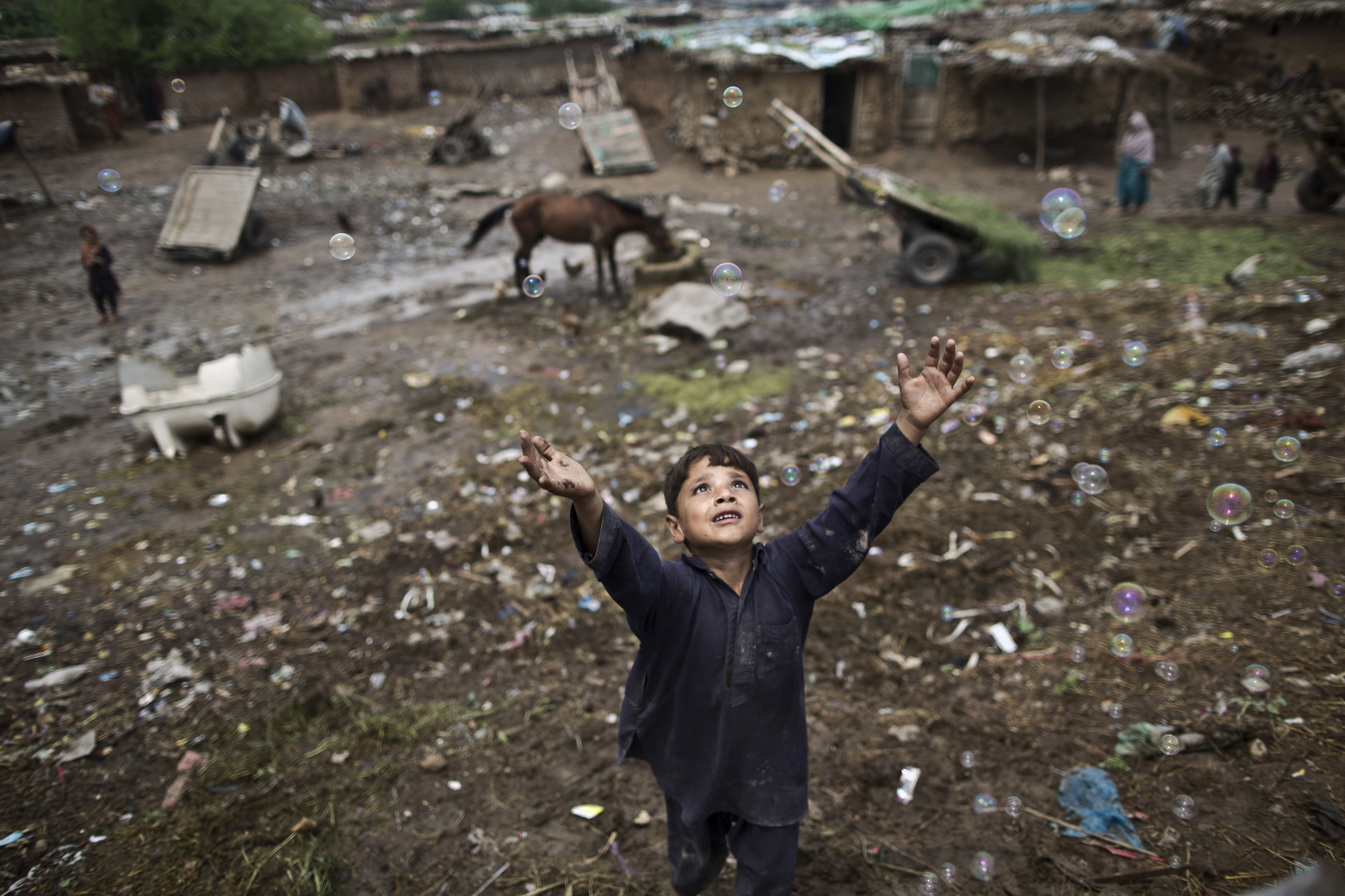 Aug. 8, 2014. An Afghan refugee child chases bubbles released by other children, while playing on the outskirts of Islamabad, Pakistan.