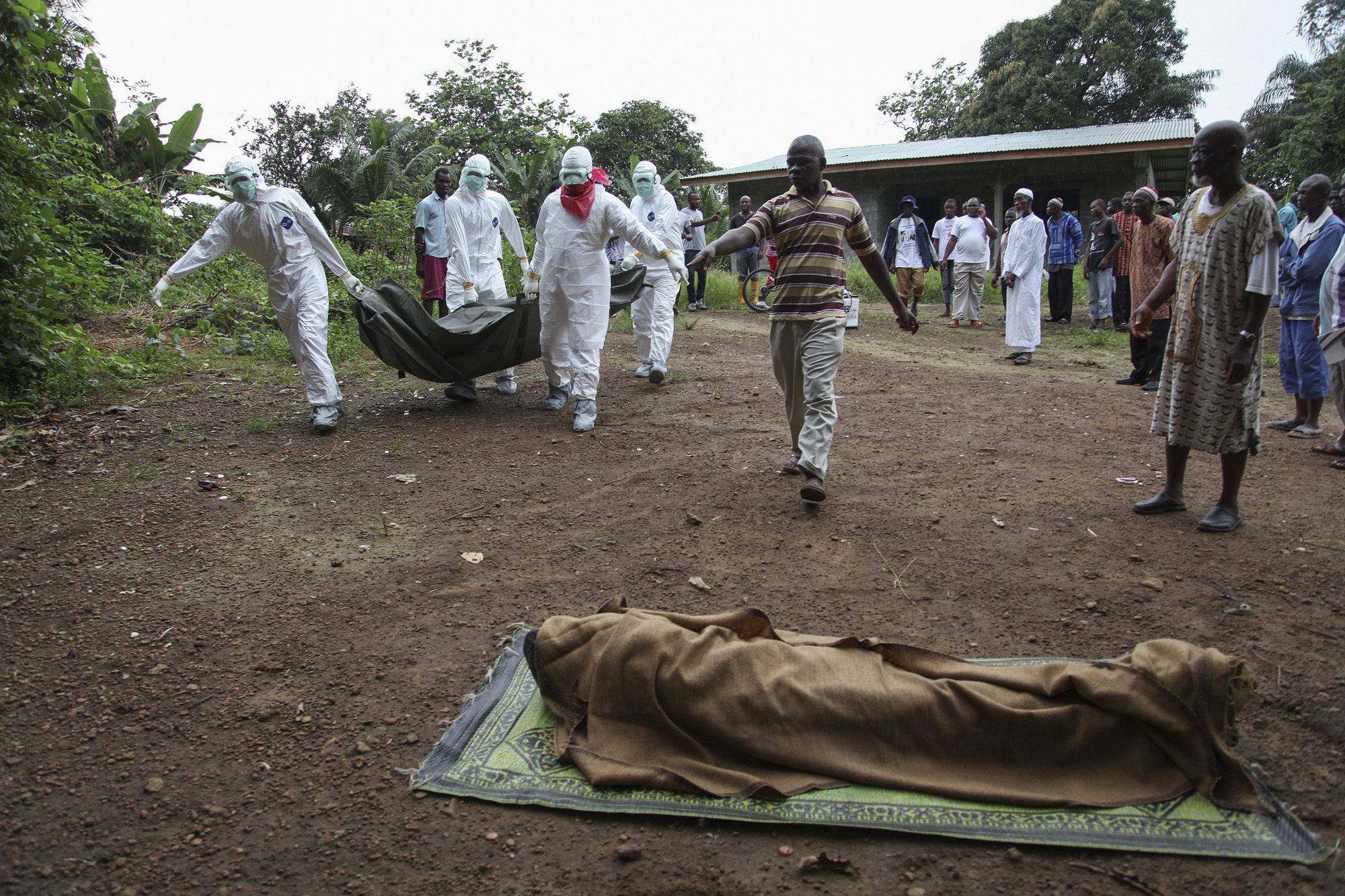 Liberian nurses carry the body of an Ebola victim on the way to burial in the Banjor community on the outskirts of Monrovia, Liberia, Aug. 6, 2014.