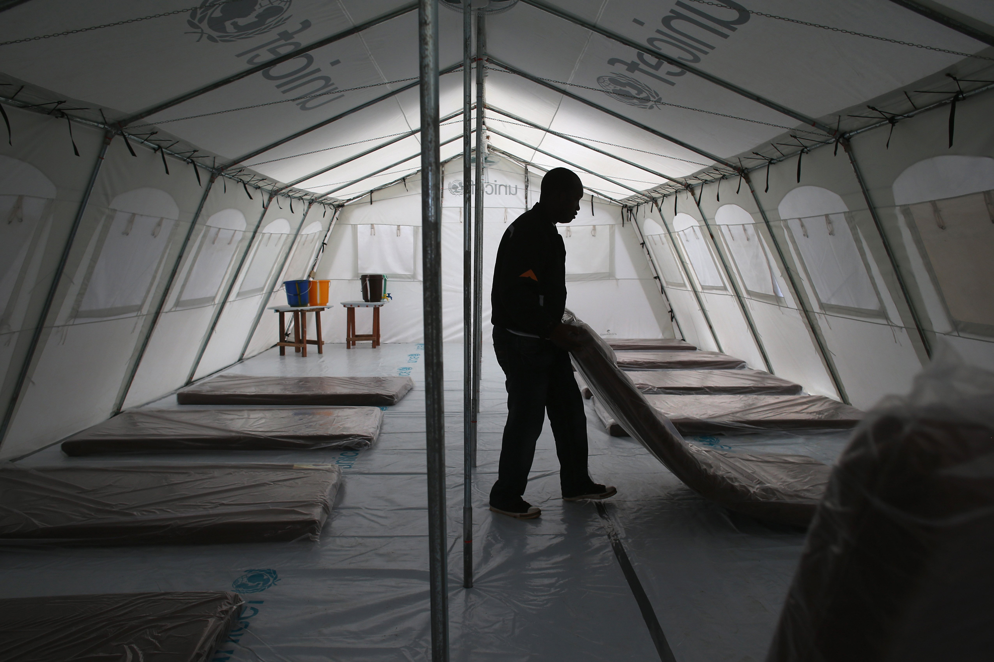 Workers prepare the new Doctors Without Borders, Ebola treatment center on Aug. 17, 2014 near Monrovia, Liberia. Tents at the center were provided by UNICEF.