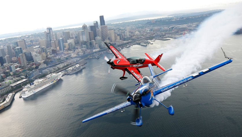 Pilots John Klatt, right, flying the blue Air National Guard MX-S airplane, and Jeff Boerboon, left, flying the red Jack's Links Extra 300L airplane, fly in formation above Seattle on Aug. 2, 2014.