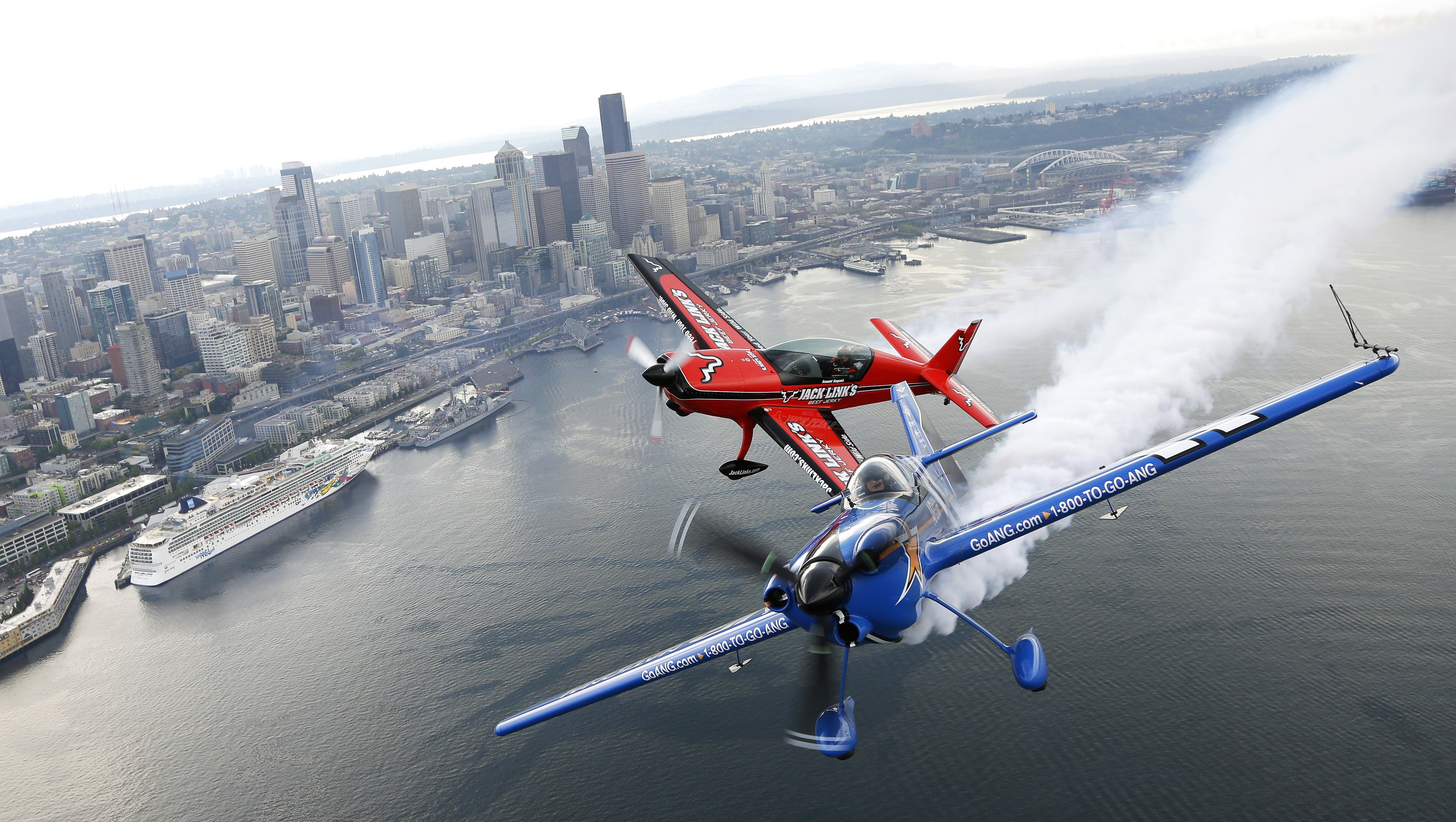 Aug. 2, 2014. Pilots John Klatt, right, flying the blue Air National Guard MX-S airplane, and Jeff Boerboon, left, flying the red Jack's Links Extra 300L airplane, fly in formation above Seattle.