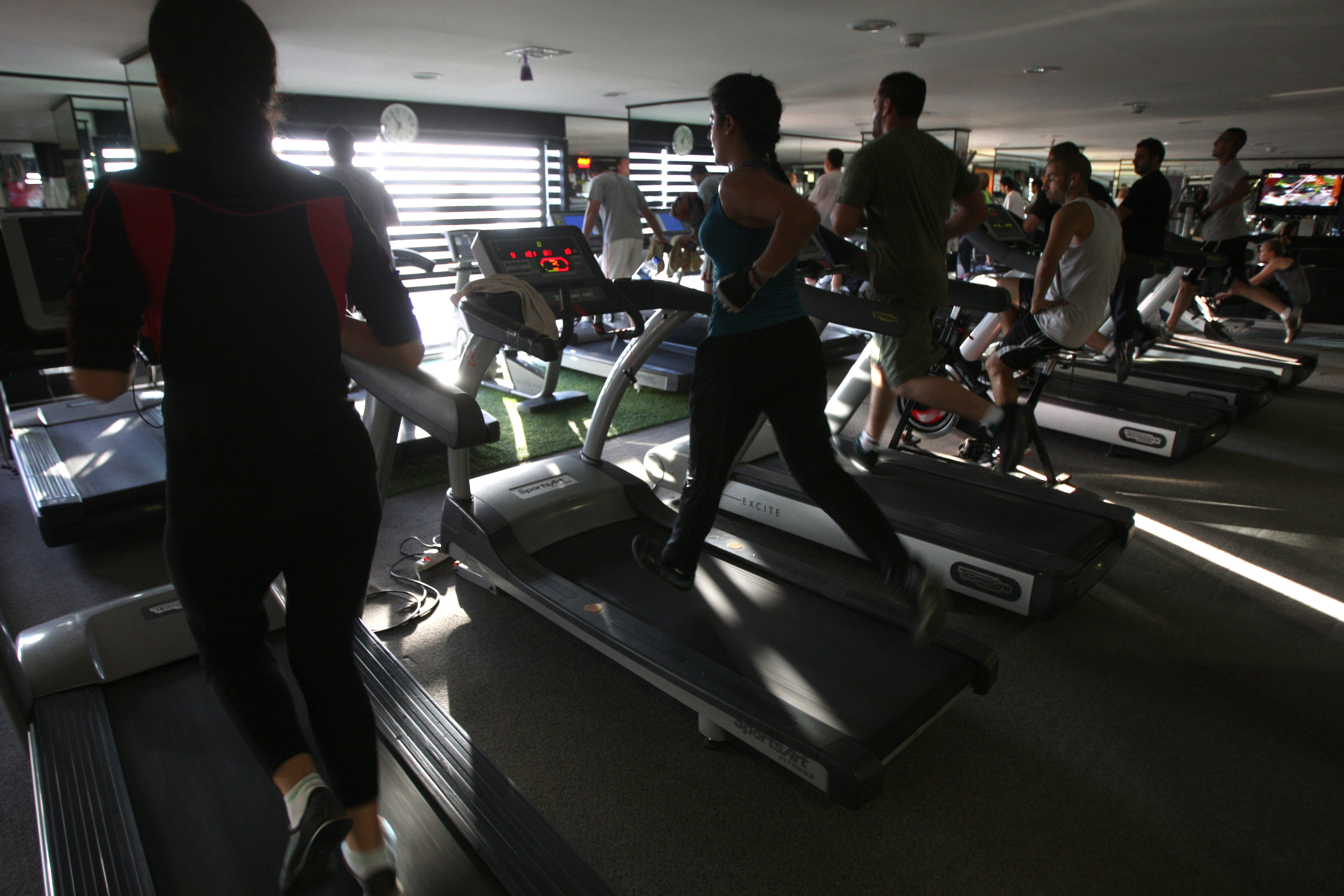 Men and women run on treadmills at a fitness gym in the West Bank city of Ramallah on June 25, 2012.
