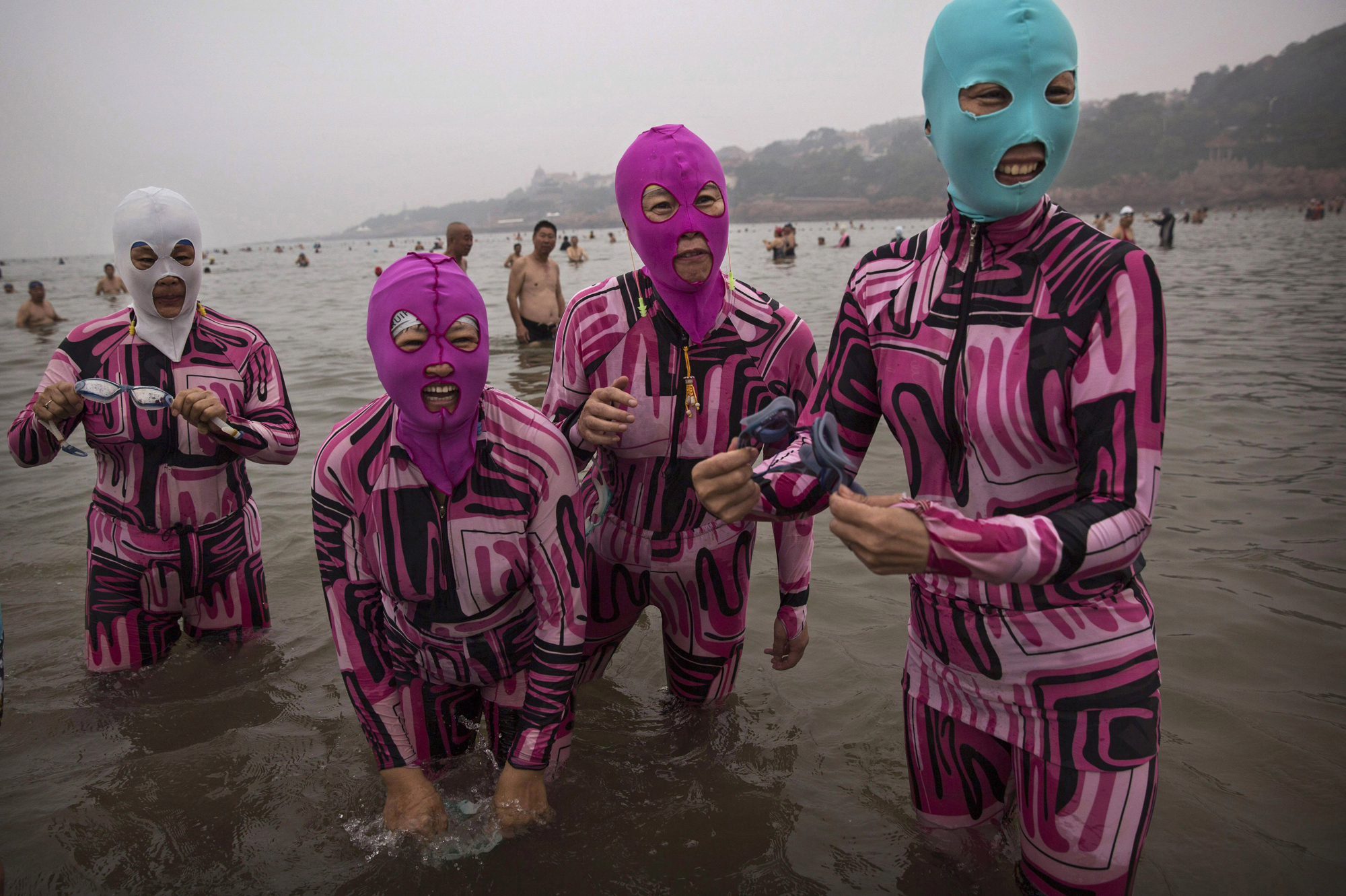 Women wear facekinis as they stand in the water on Aug. 20, 2014, on the Yellow Sea in Qingdao.