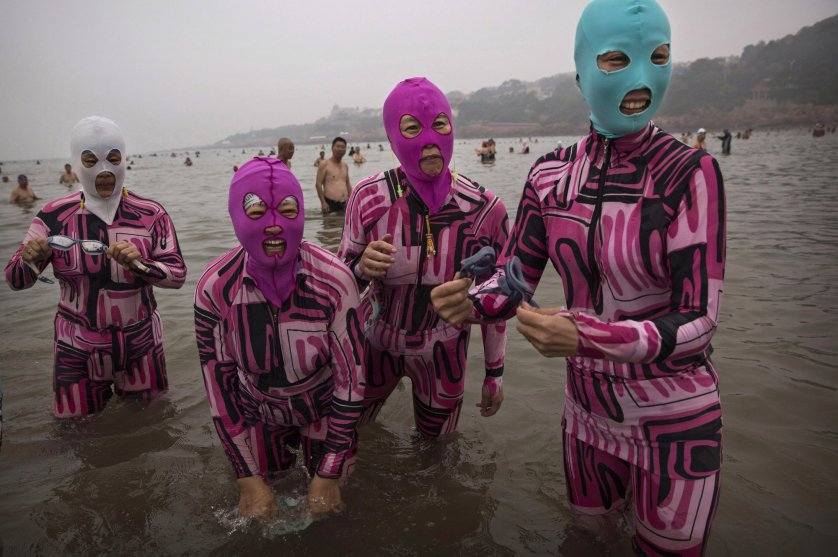 Chinese women wear face-kinis as they stand in the water on Aug. 20, 2014 on the Yellow Sea in Qingdao, China.
