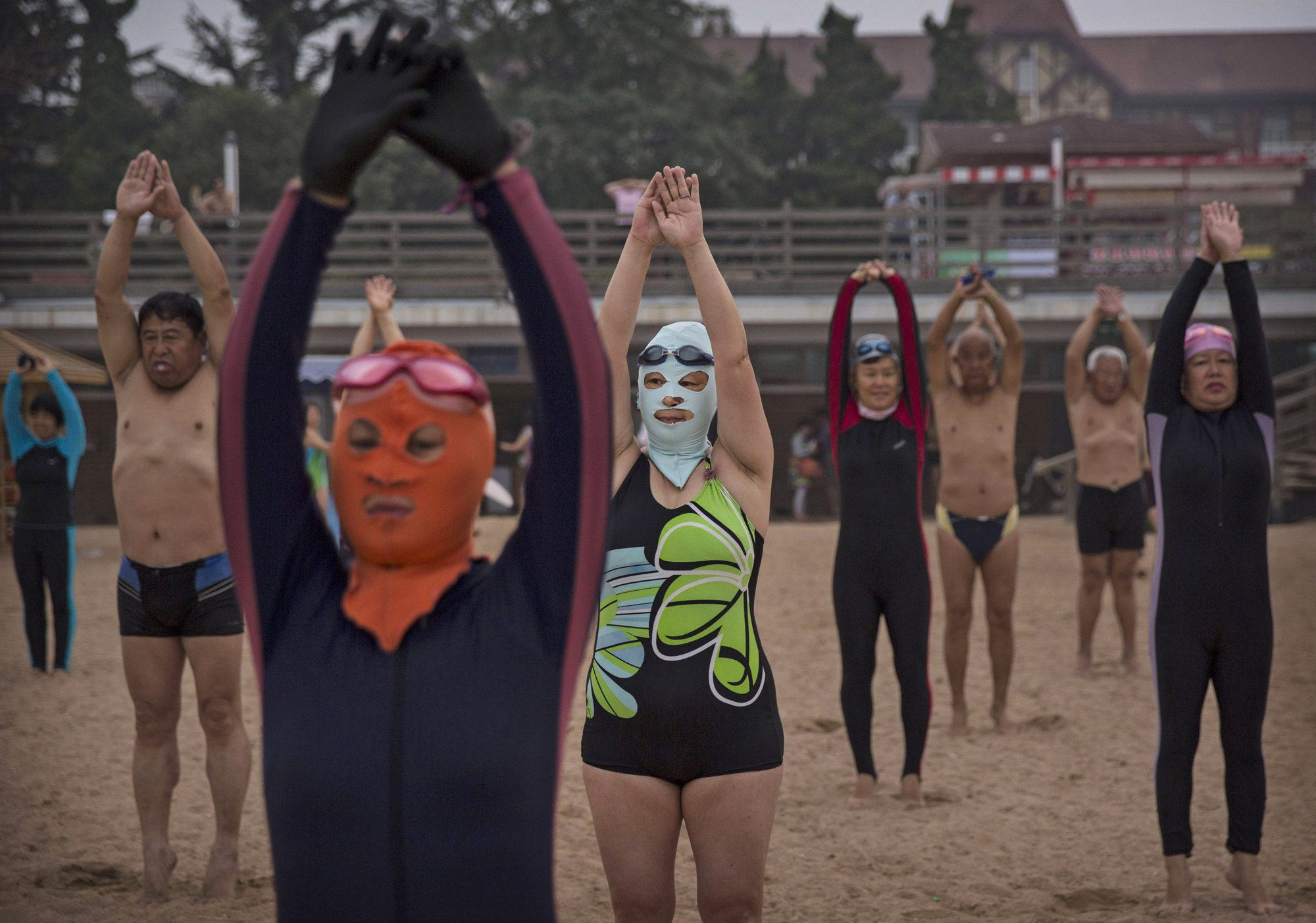 Women wear facekinis as they exercise on the beach on Aug. 20, 2014, on the Yellow Sea in Qingdao.