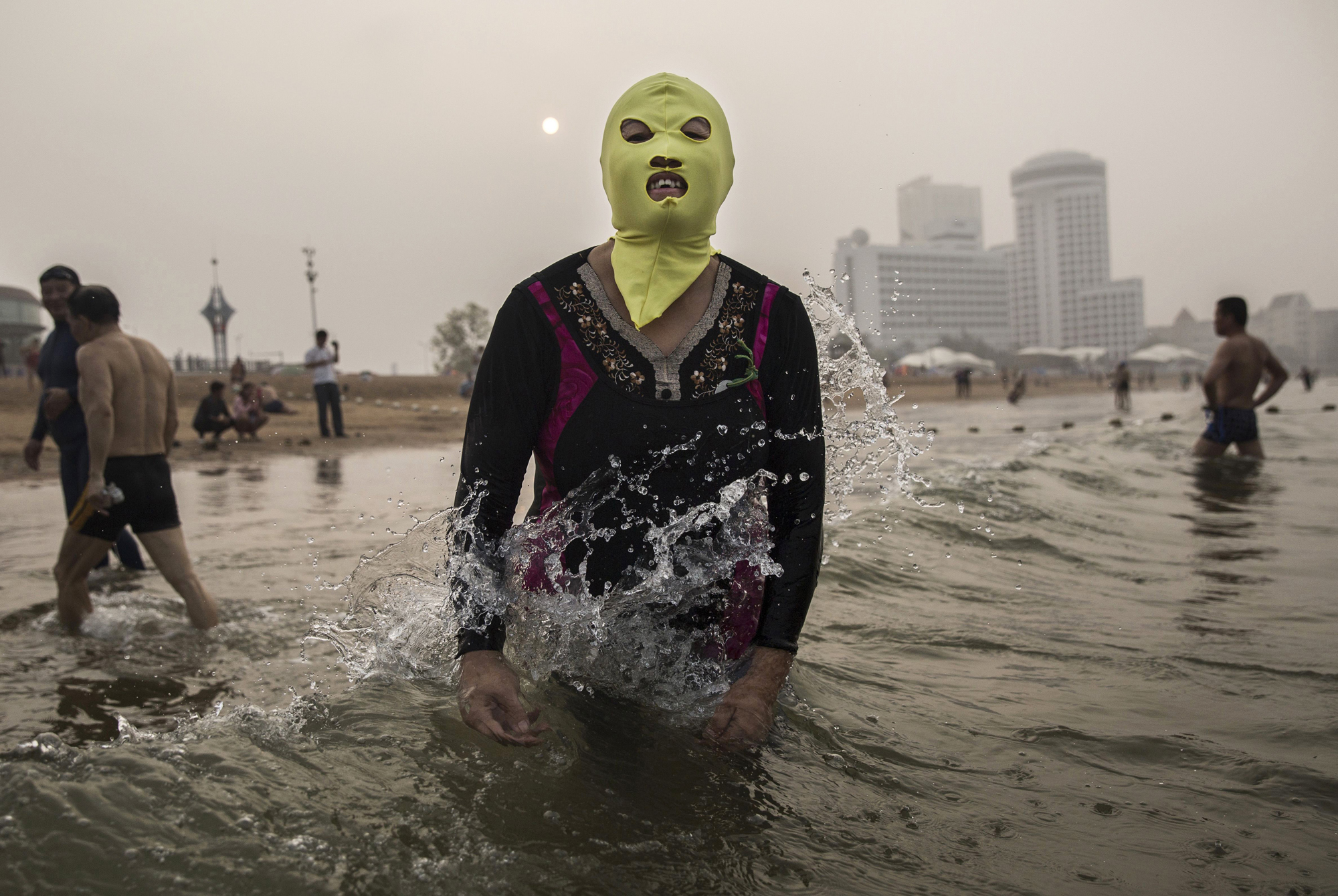 A woman wears a facekini as she gets wet before swimming on Aug. 22, 2014, on the Yellow Sea in Qingdao.