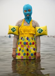 A Chinese woman wears a face-kini as she poses on Aug. 21, 2014 in the Yellow Sea in Qingdao.