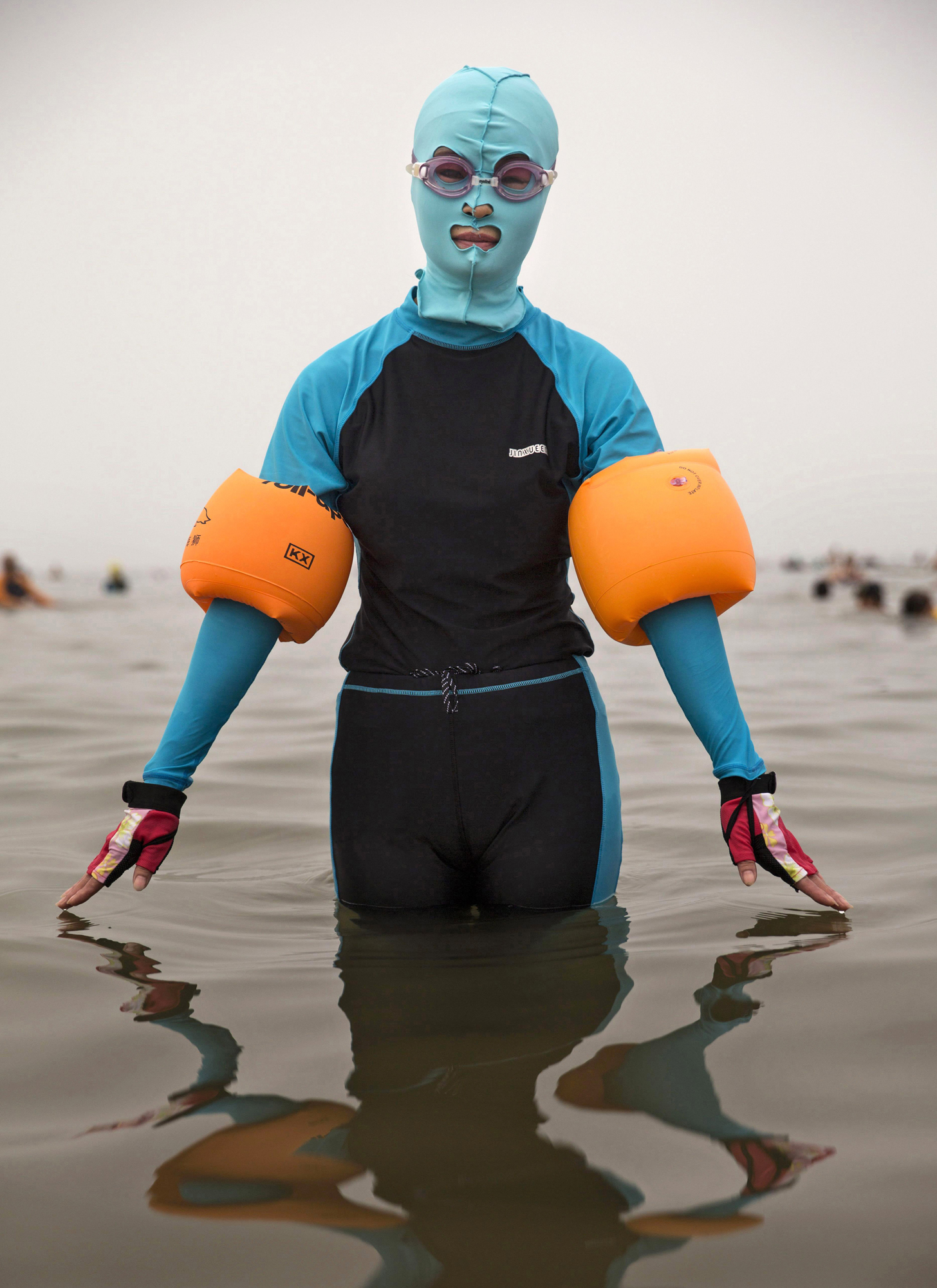 A woman wears a facekini as she poses on Aug. 21, 2014, in the Yellow Sea in Qingdao.